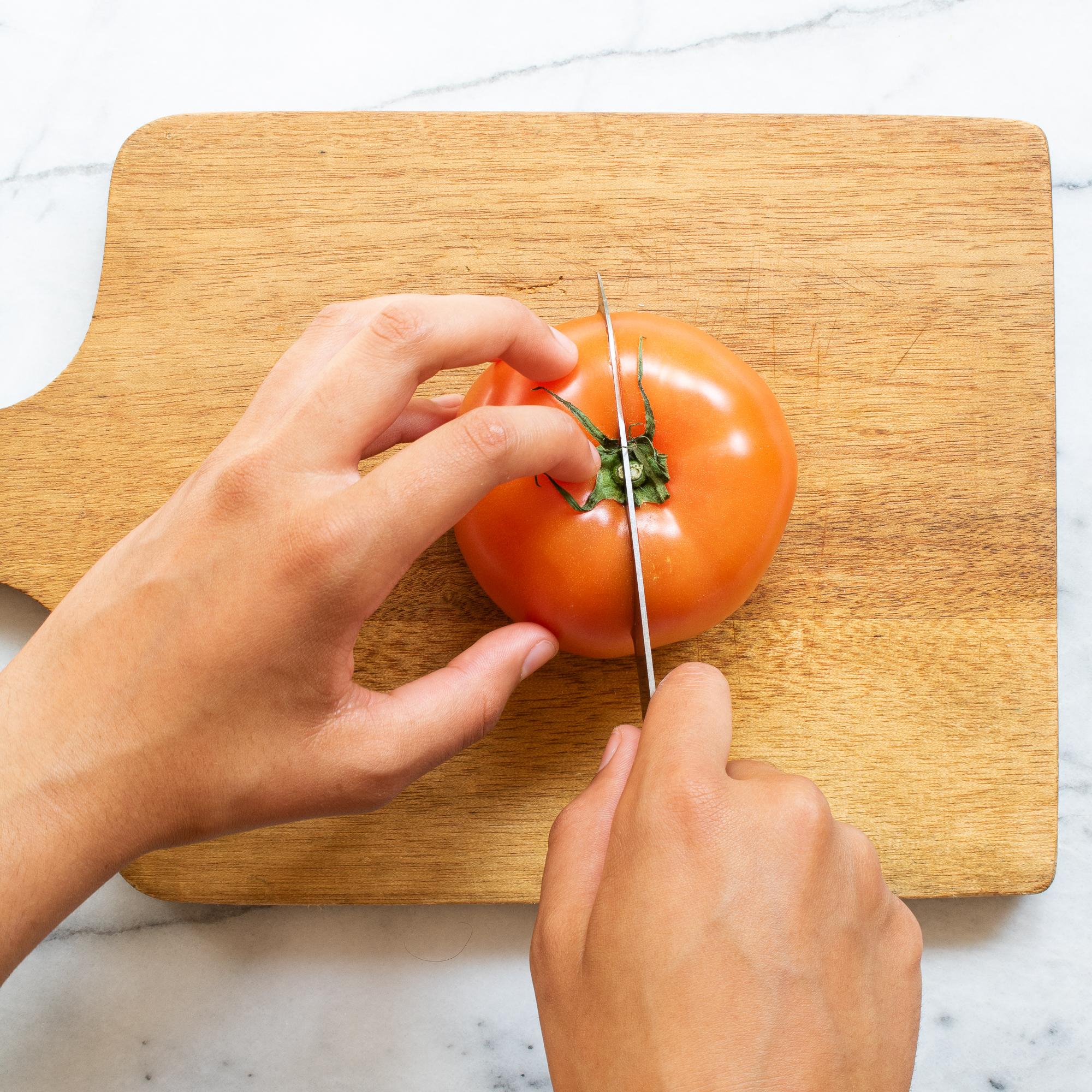 hands using a knife to cut a tomato into wedges on a wood cutting board