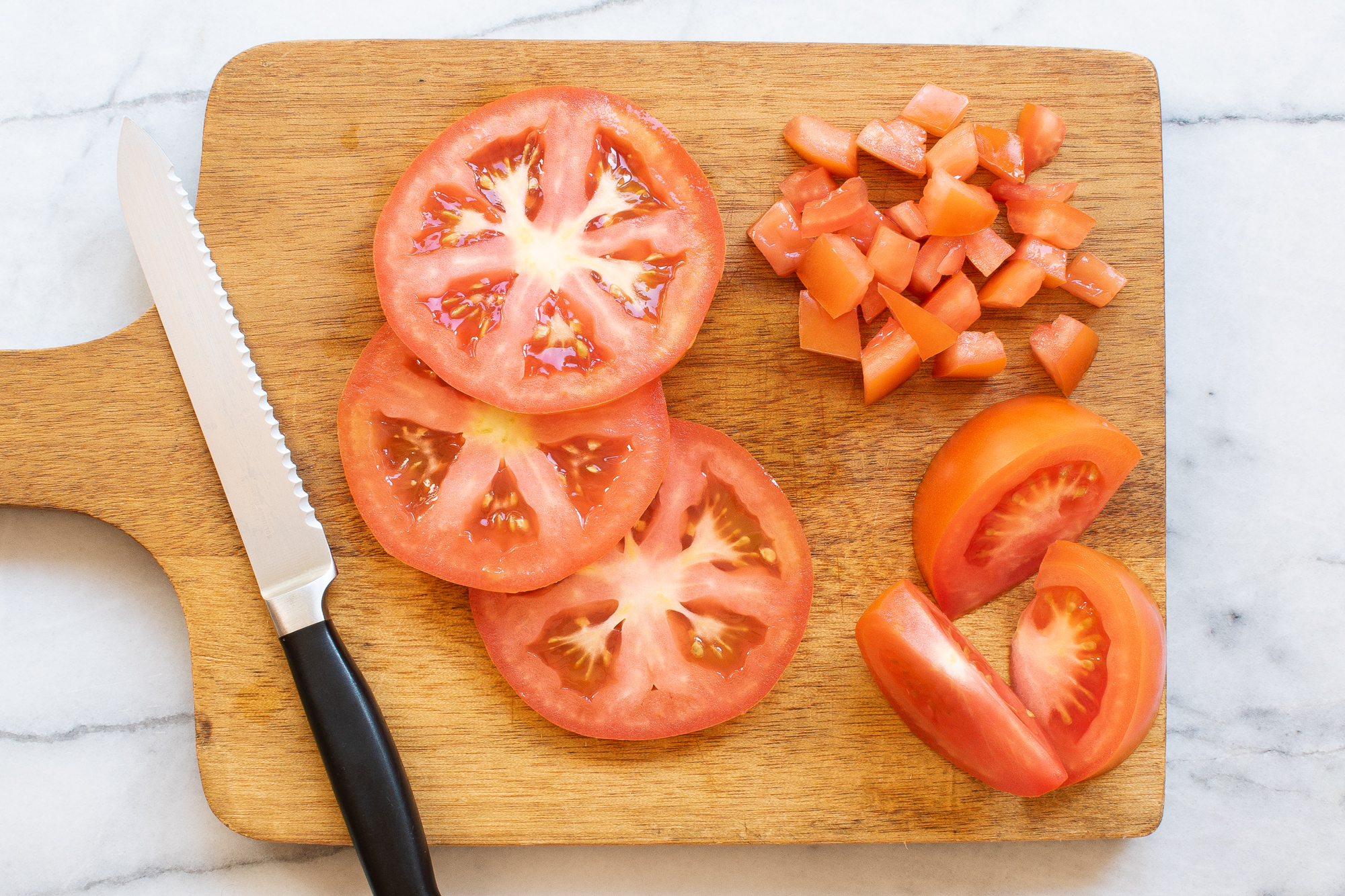 A cutting board with a knife and different cutting styles of tomatoes on it