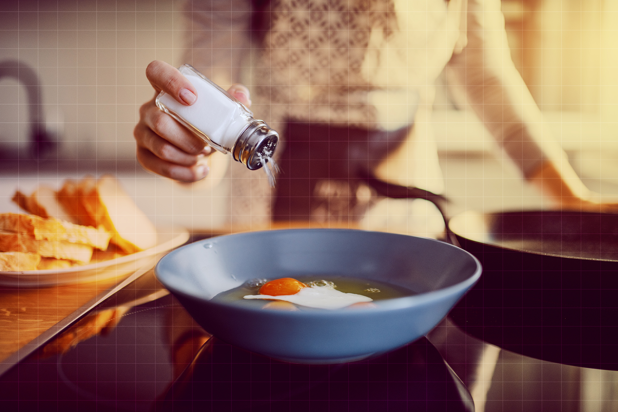 Close up of caucasian woman adding salt in sunny side up eggs while standing in kitchen next to stove.