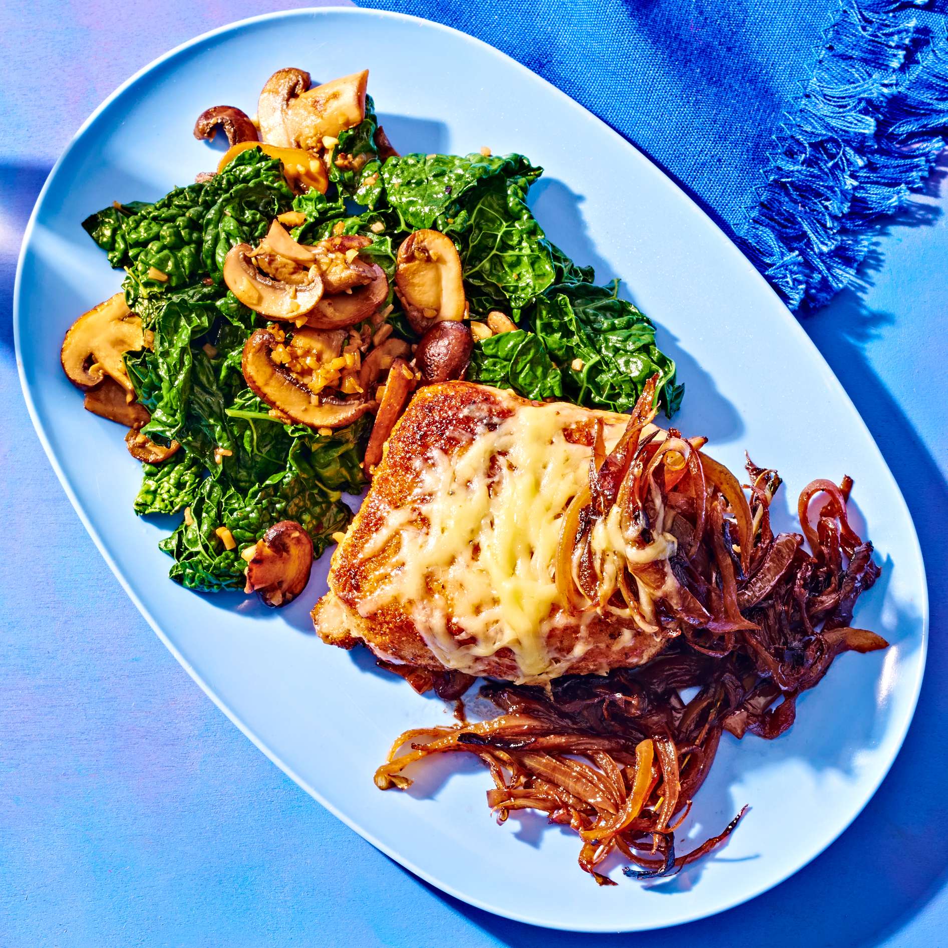 Cheesy Smothered Pork Chops with Garlicky Mushrooms & Kale