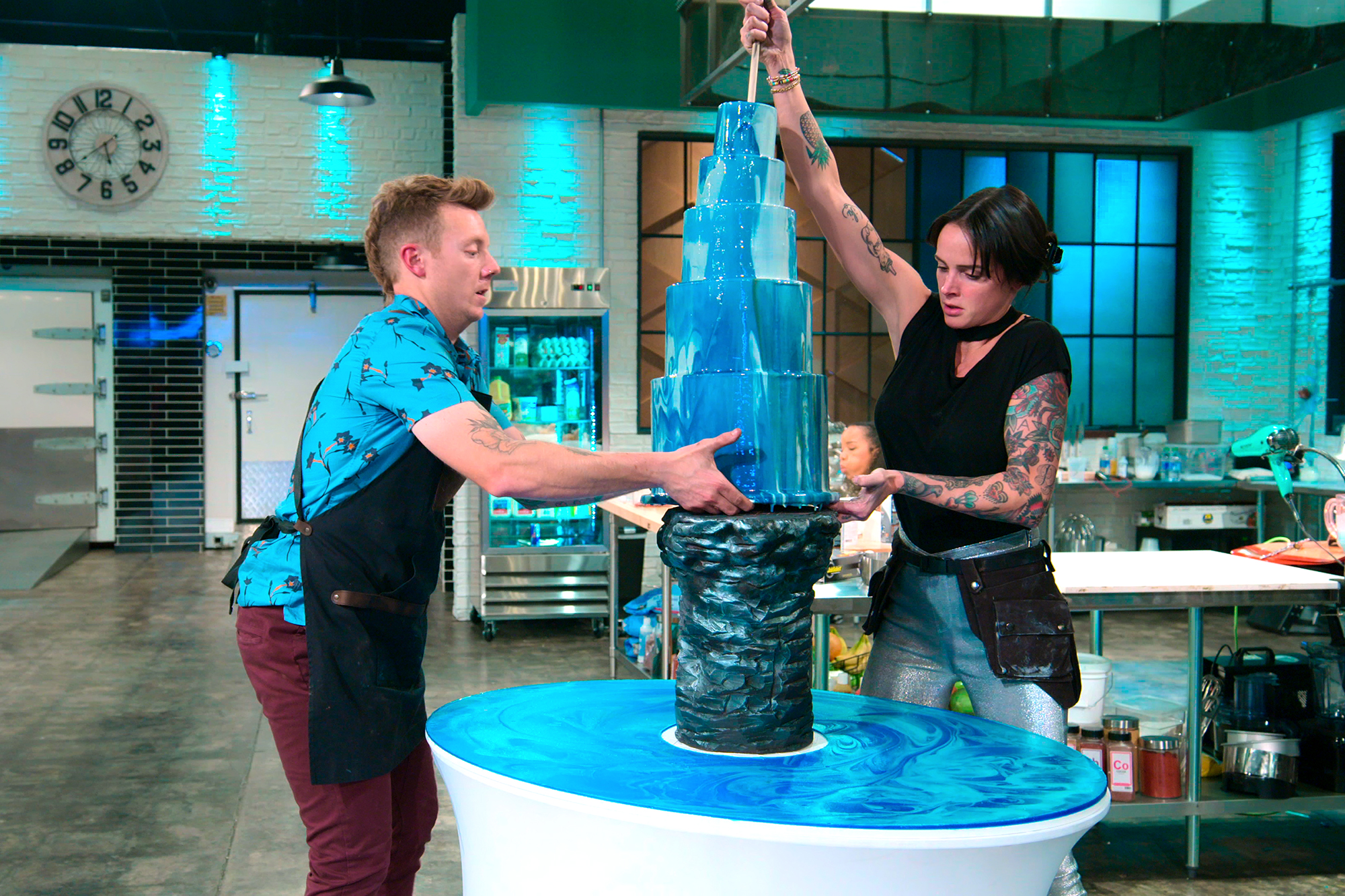 two people in an industrial kitchen working on a large 5 layer cake dripping in blue