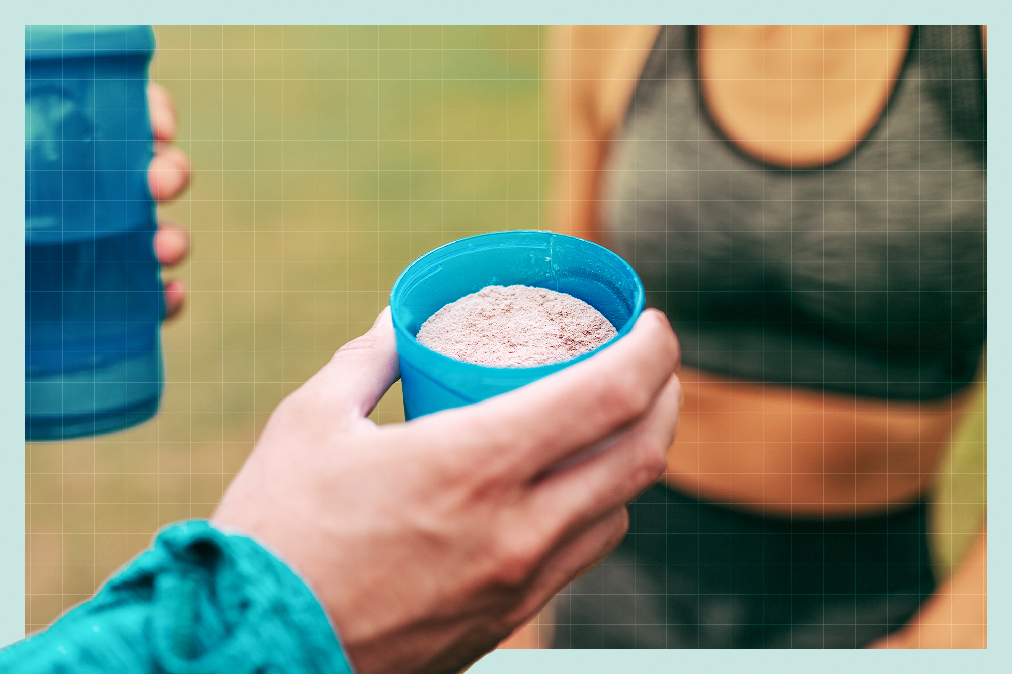 A hand holding a container full of protein powder ready to go into a protein shake. in the background is a shake bottle and a woman in workout clothes