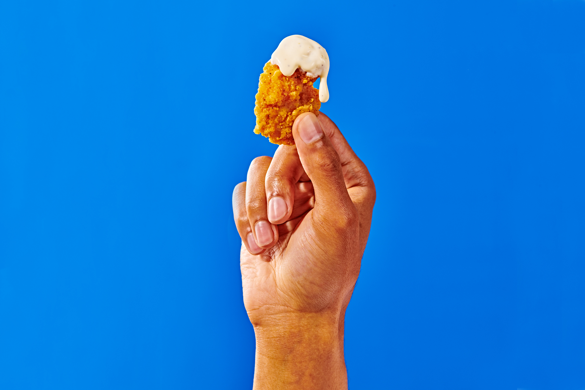 A hand holding a chicken nugget on a designed background