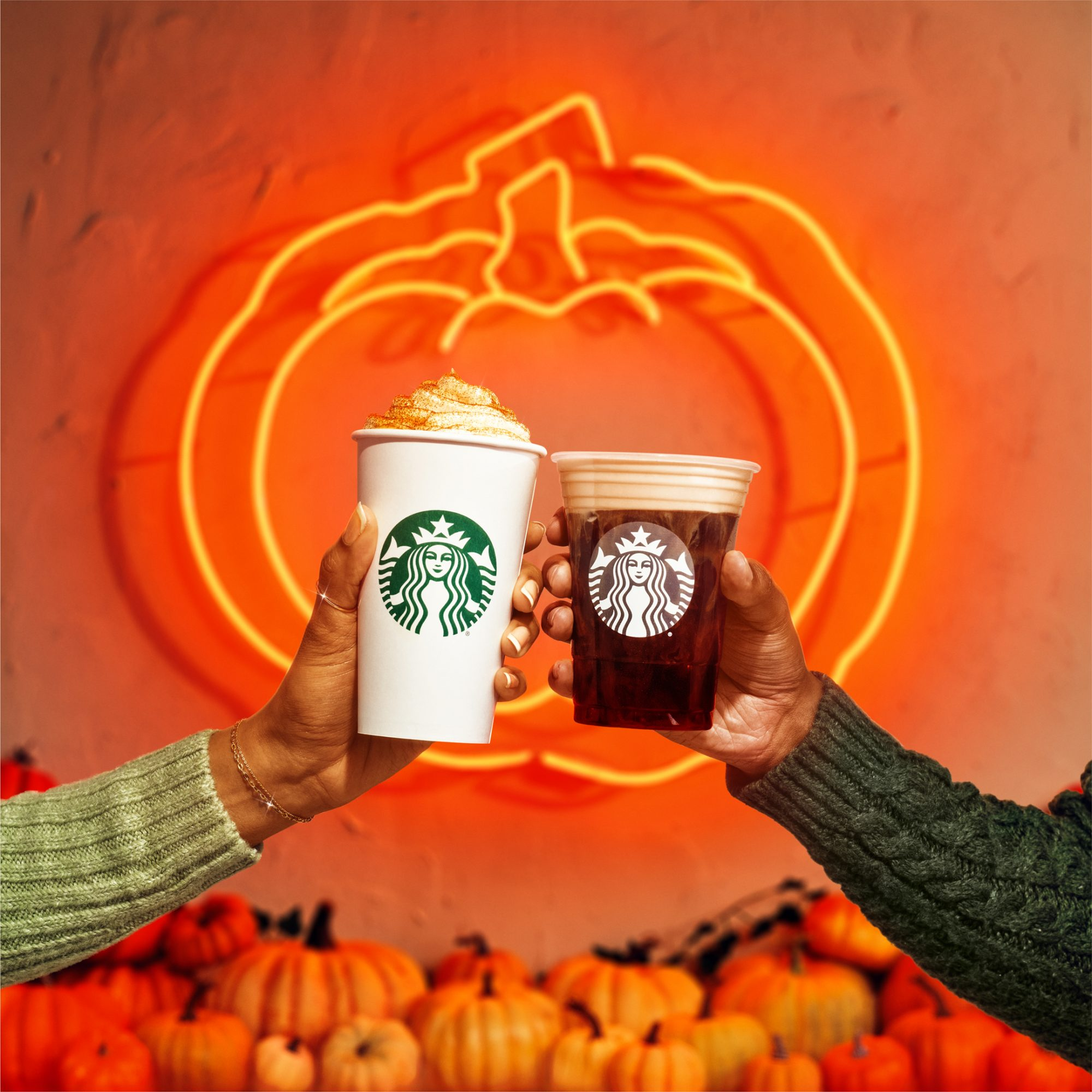 two hands holding a hot latte and a cold brew in front of a neon pumpkin sign