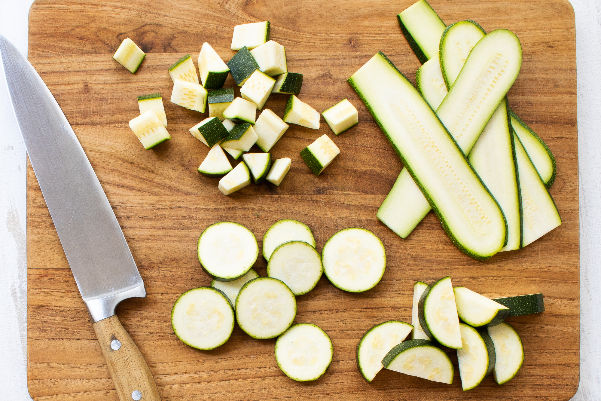 A knife on a wood cutting board next to pieces of zucchini cut using different methods