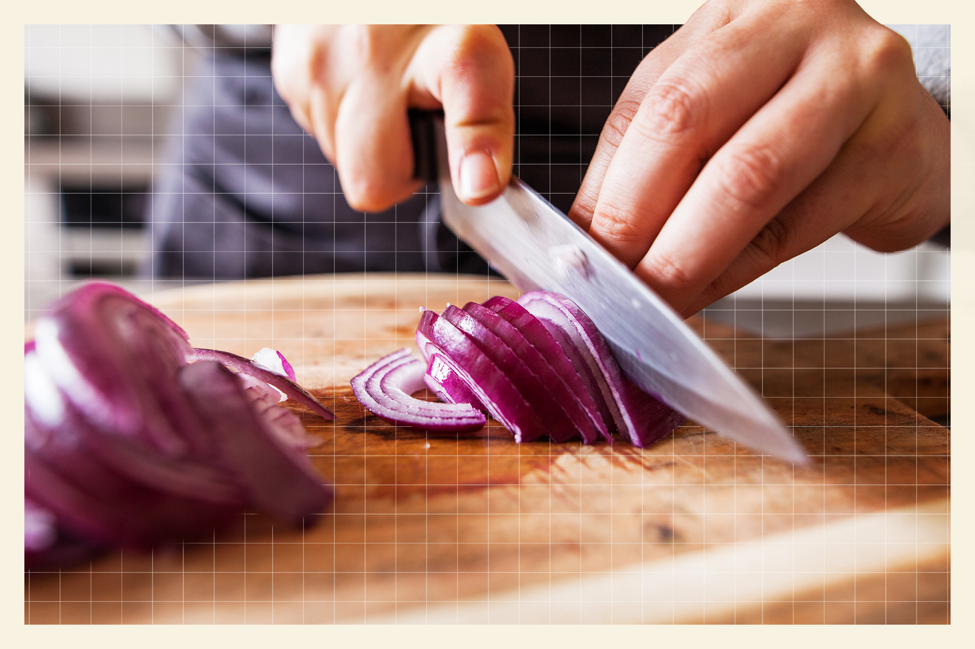 close up of hand's cutting a red onion