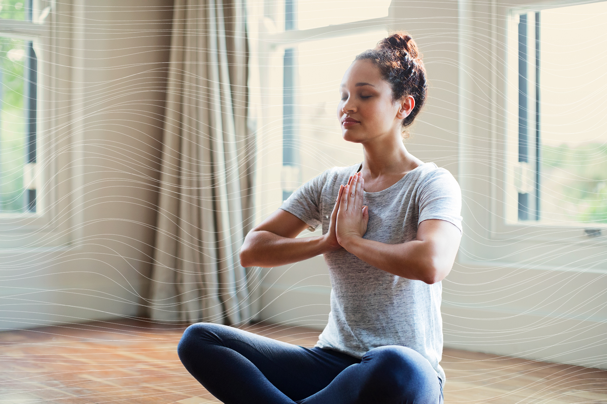 Young woman meditating with hands joined at home