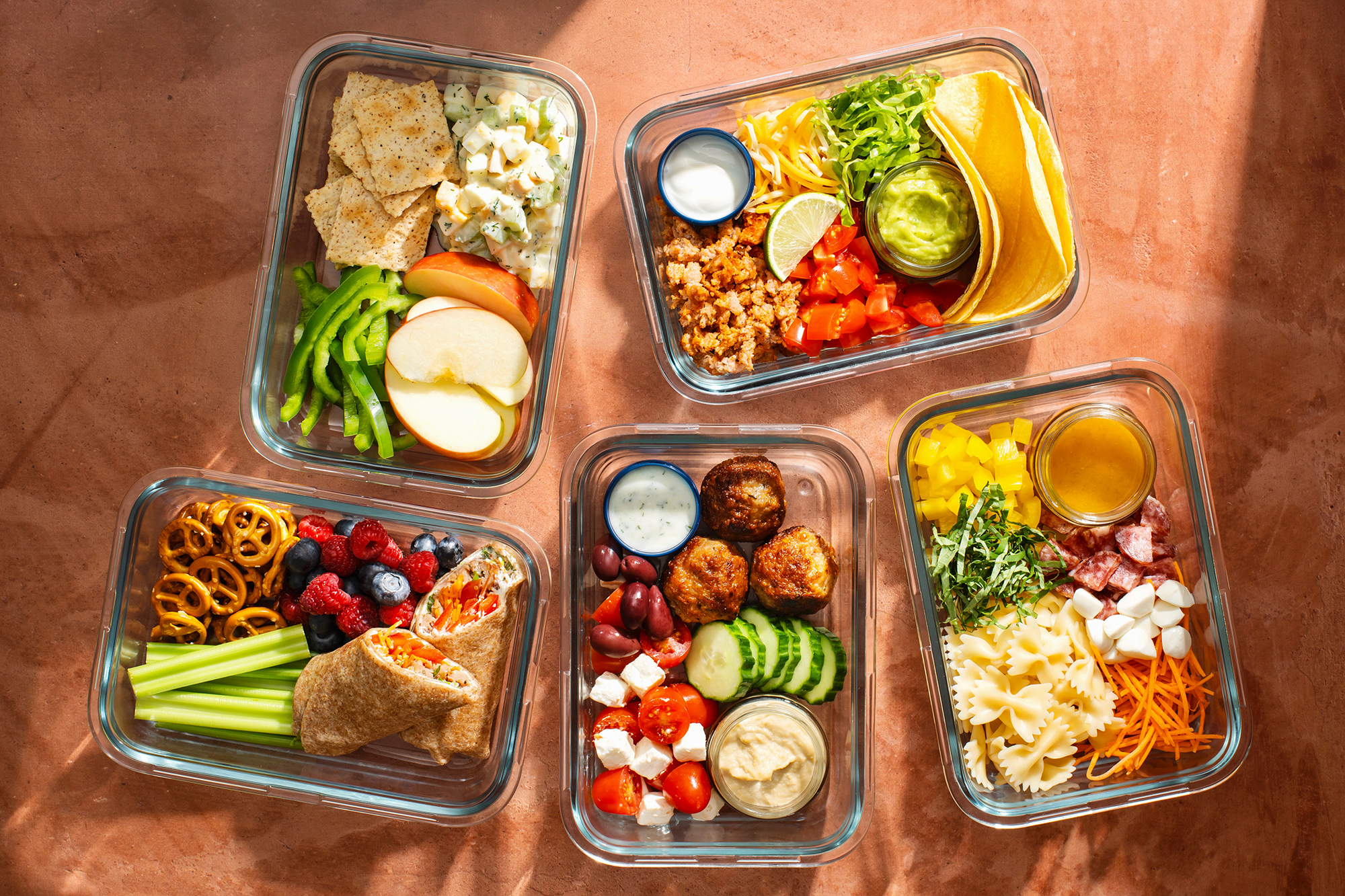 Several glass lunch boxes with a variety of foods packed in them on a terracotta colored surface