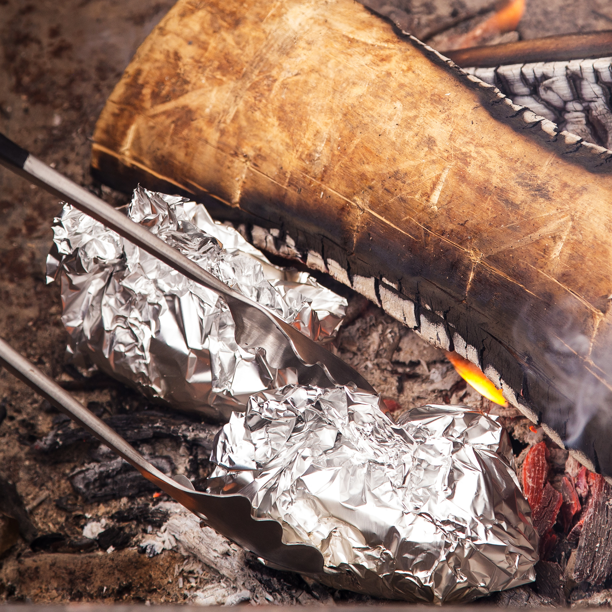 Two baked potatoes wrapped in tin foil being turned in a campfire