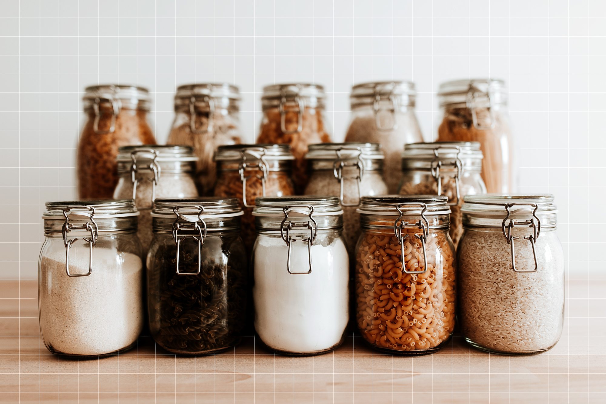 Glass jars full with dried uncooked food ingredients.