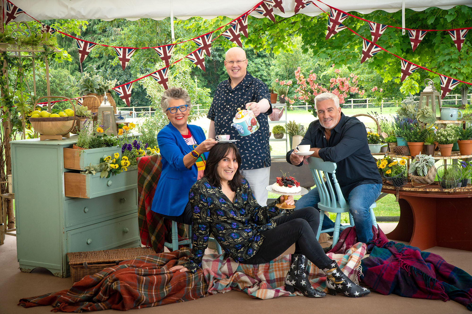 A portrait of the four hosts of Great British Baking Show