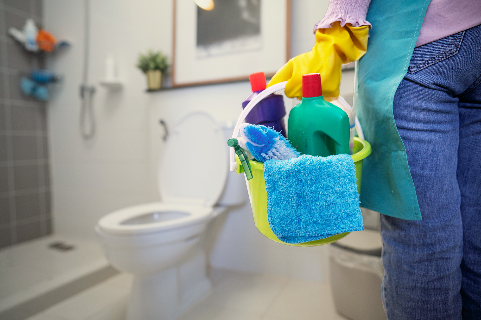 The cleaning woman is standing in the bathroom holding a blue bucket full of chemicals and cleaning utensils
