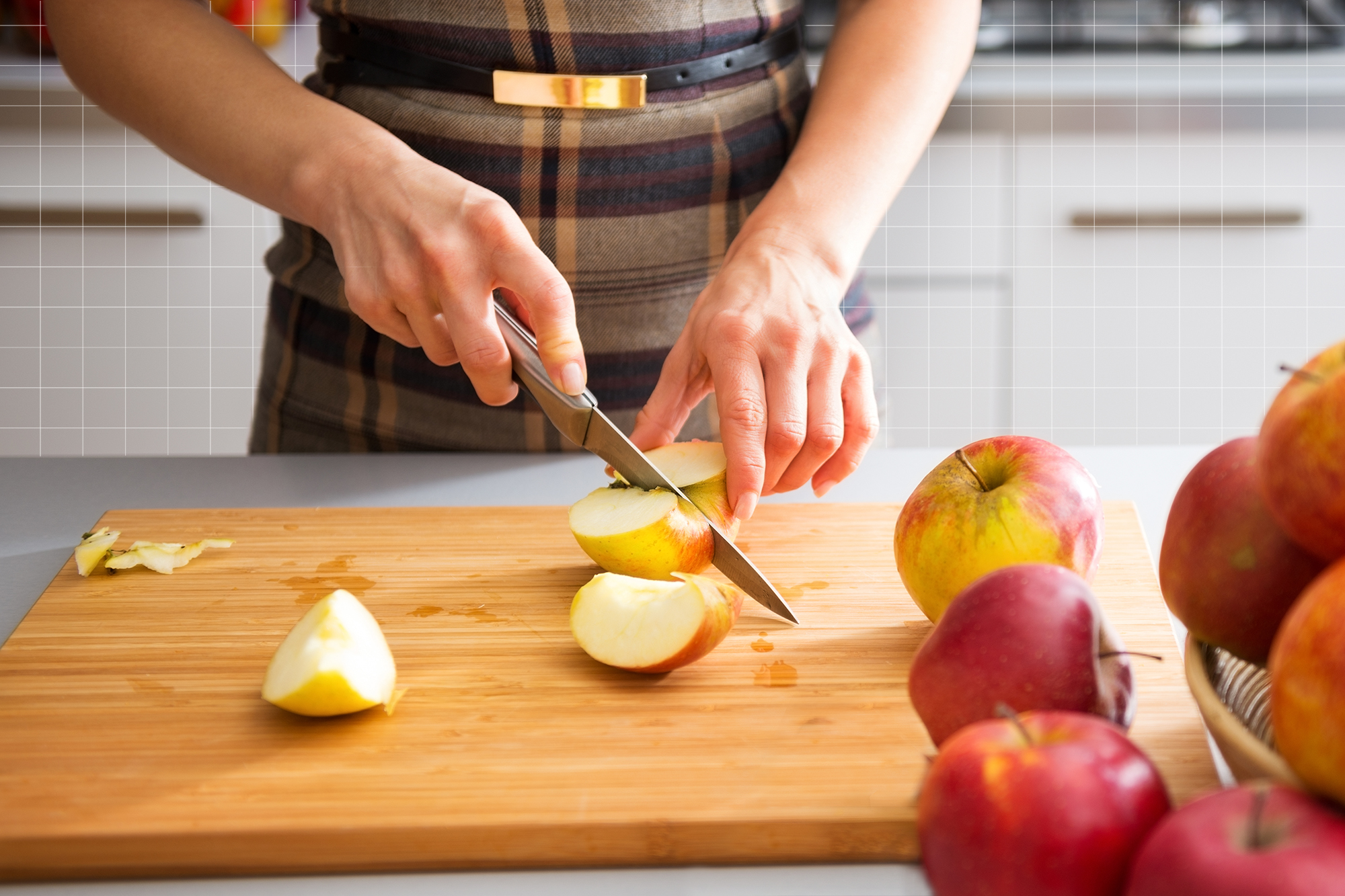 Woman's hands cutting apples on board