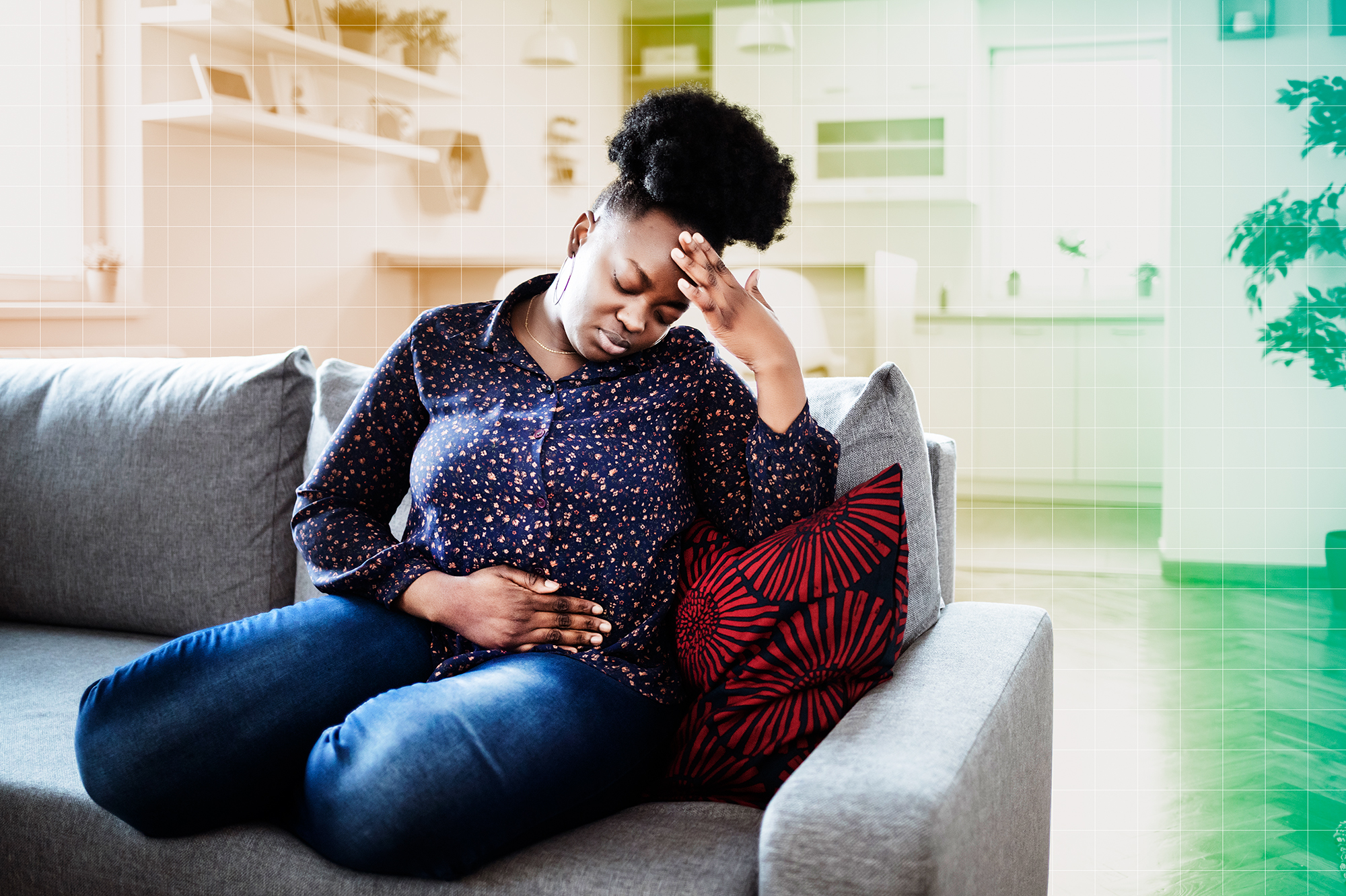 A woman sitting on a couch with a stomach ache