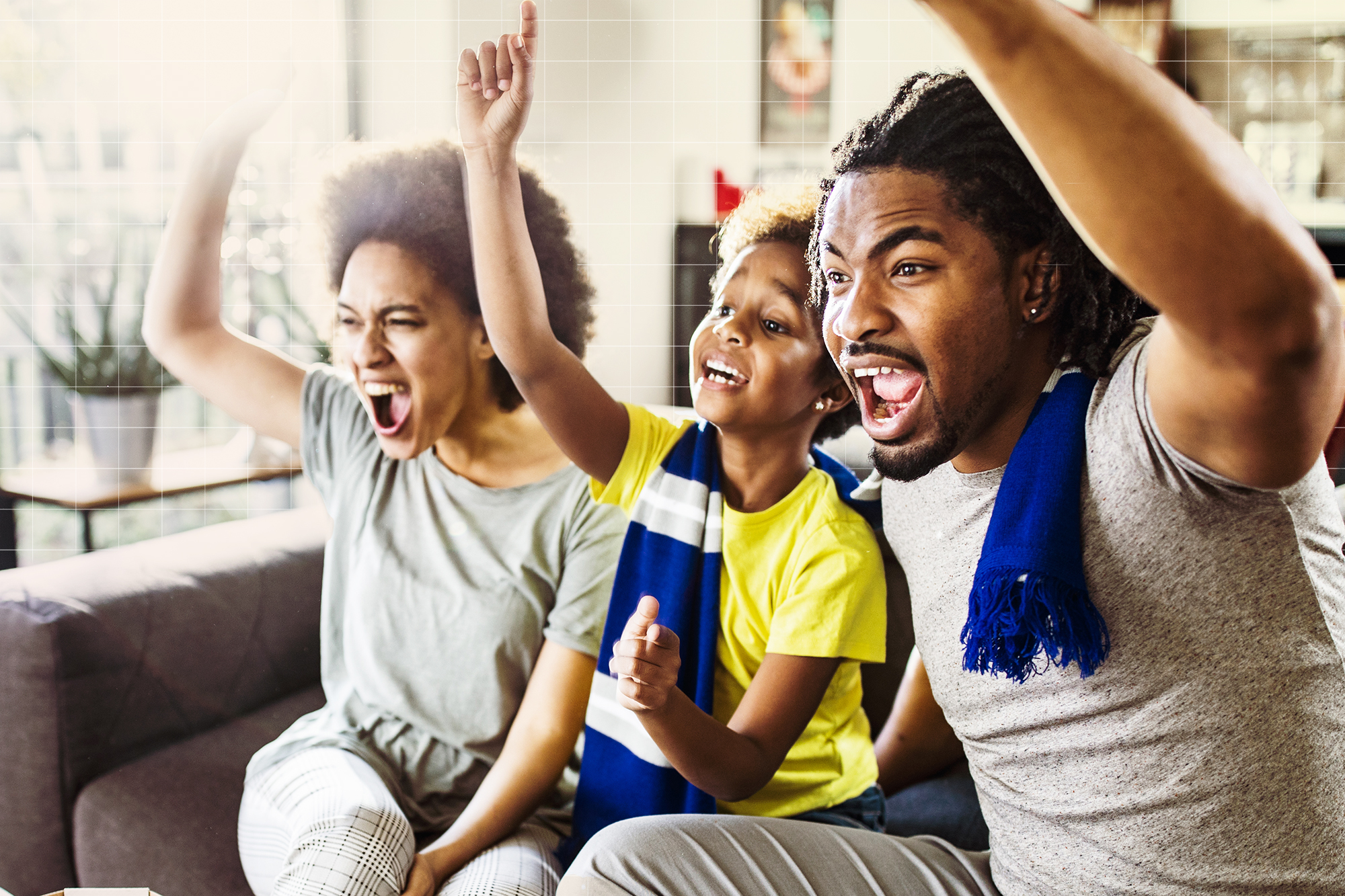 Cheerful African American family watching sports at home.