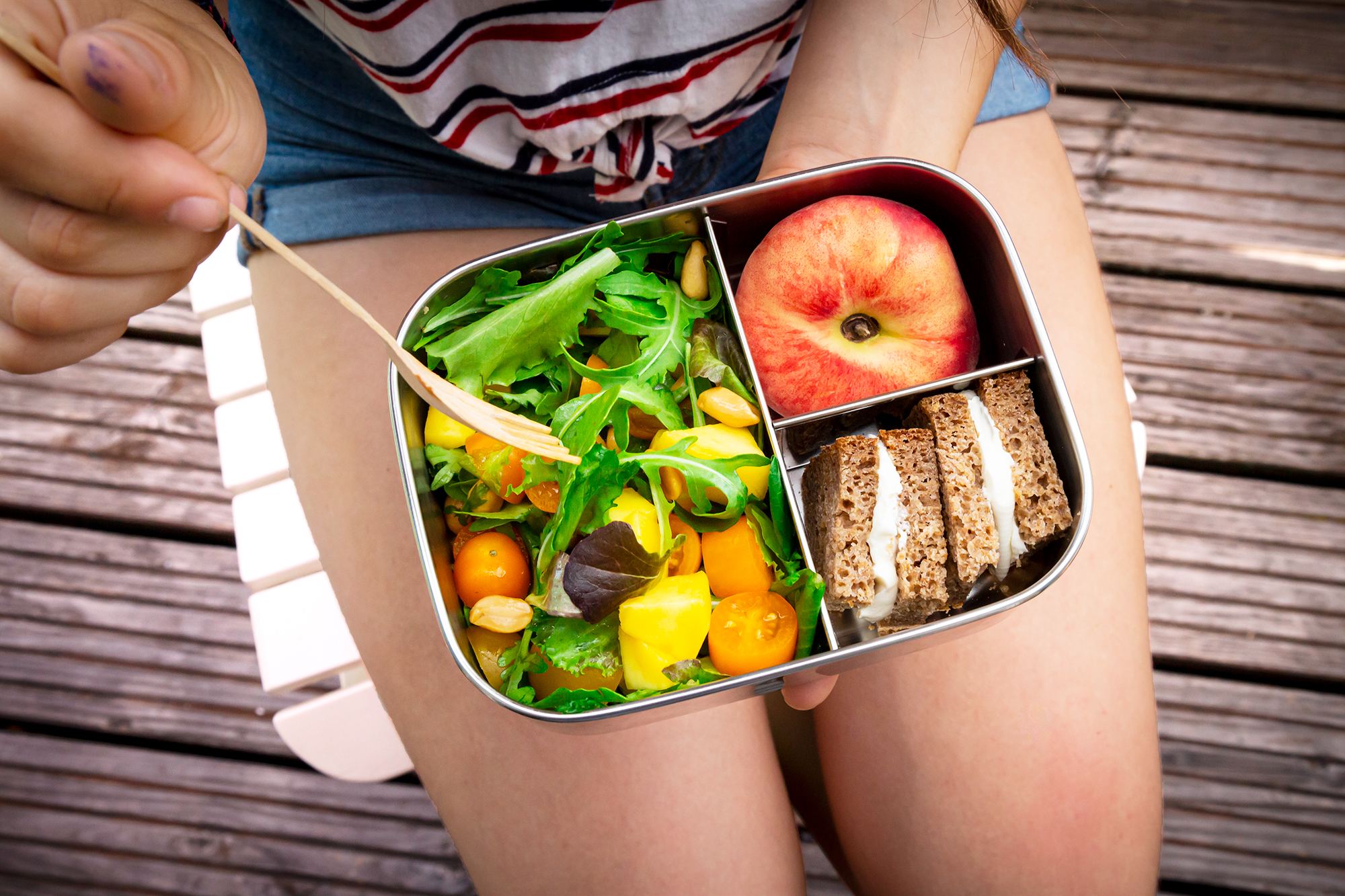 Midsection of girl having healthy lunch while sitting on bench