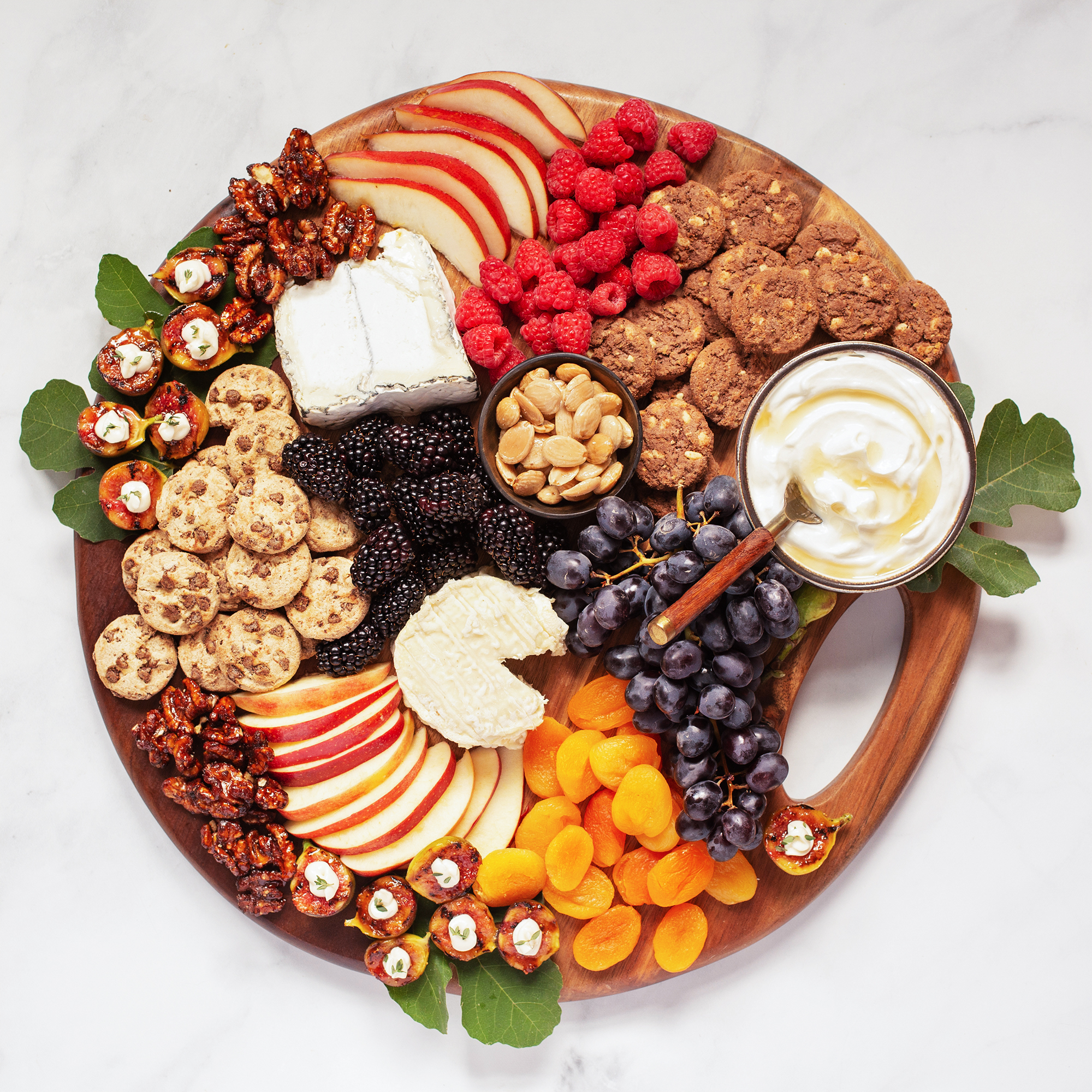 A charcuterie board with fruits, cheeses, and Famous Amos Cookies.