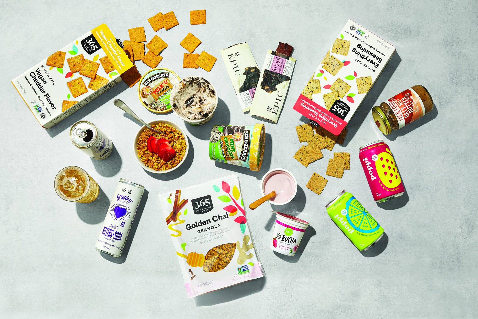 A variety of snacks from Whole Foods on a grey surface