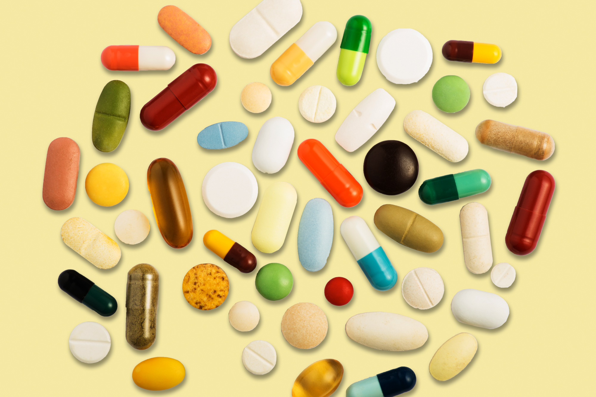 Supplement pills on pale yellow background