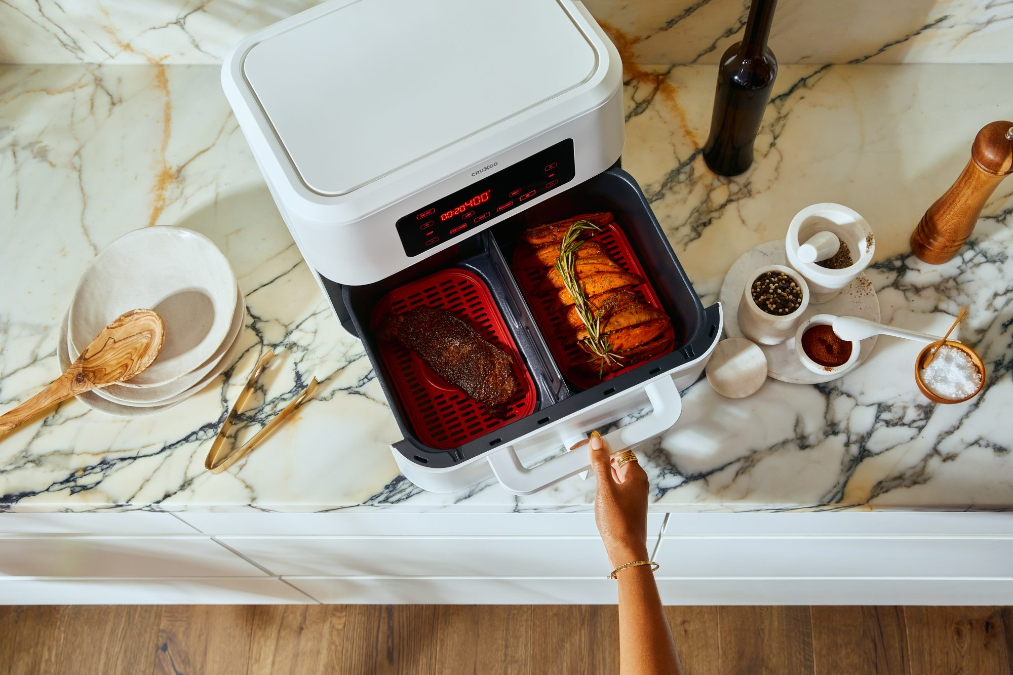 large white air fryer with a steak and potatoes in the two baskets on a large white kitchen counter