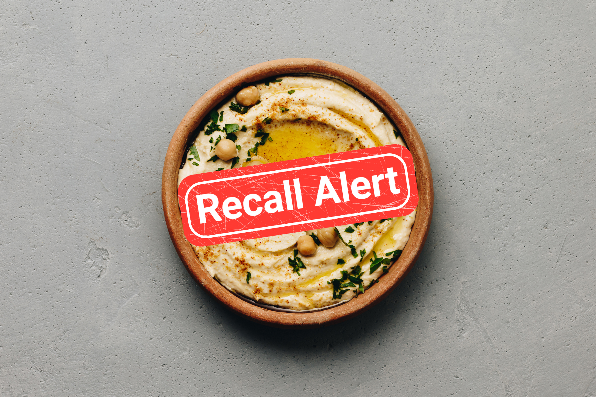 A bowl of hummus with a recall alert button over it