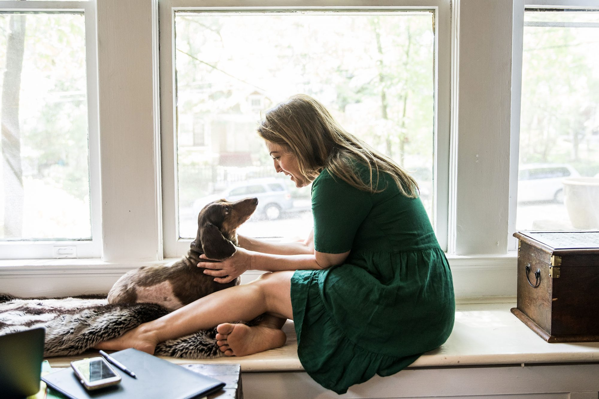woman with dachshund sitting on window seat