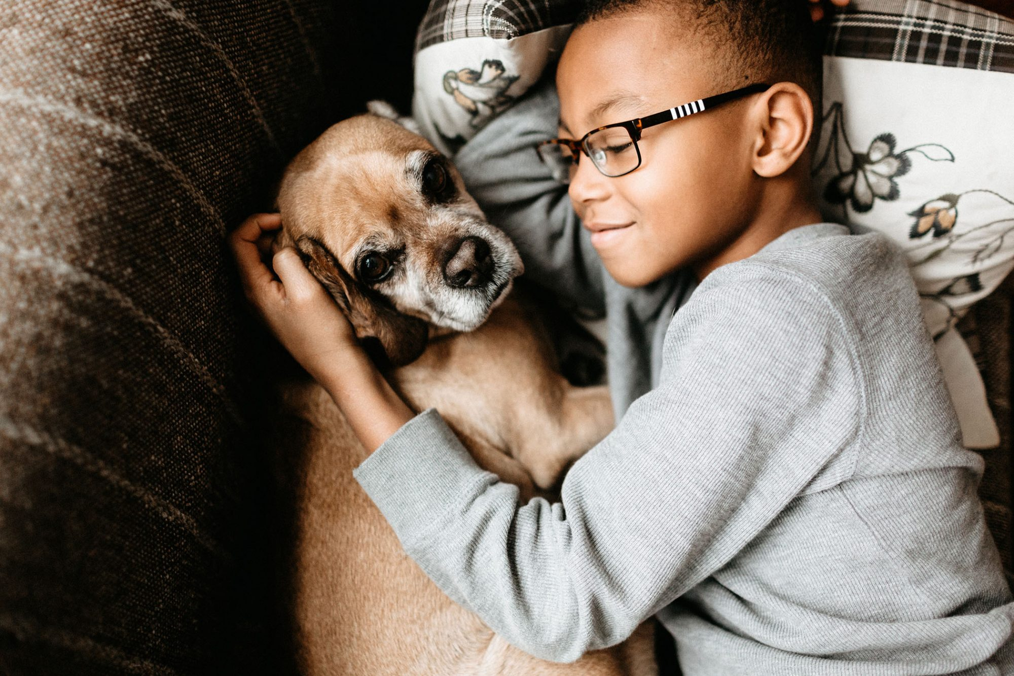 black boy snuggling dog on couch