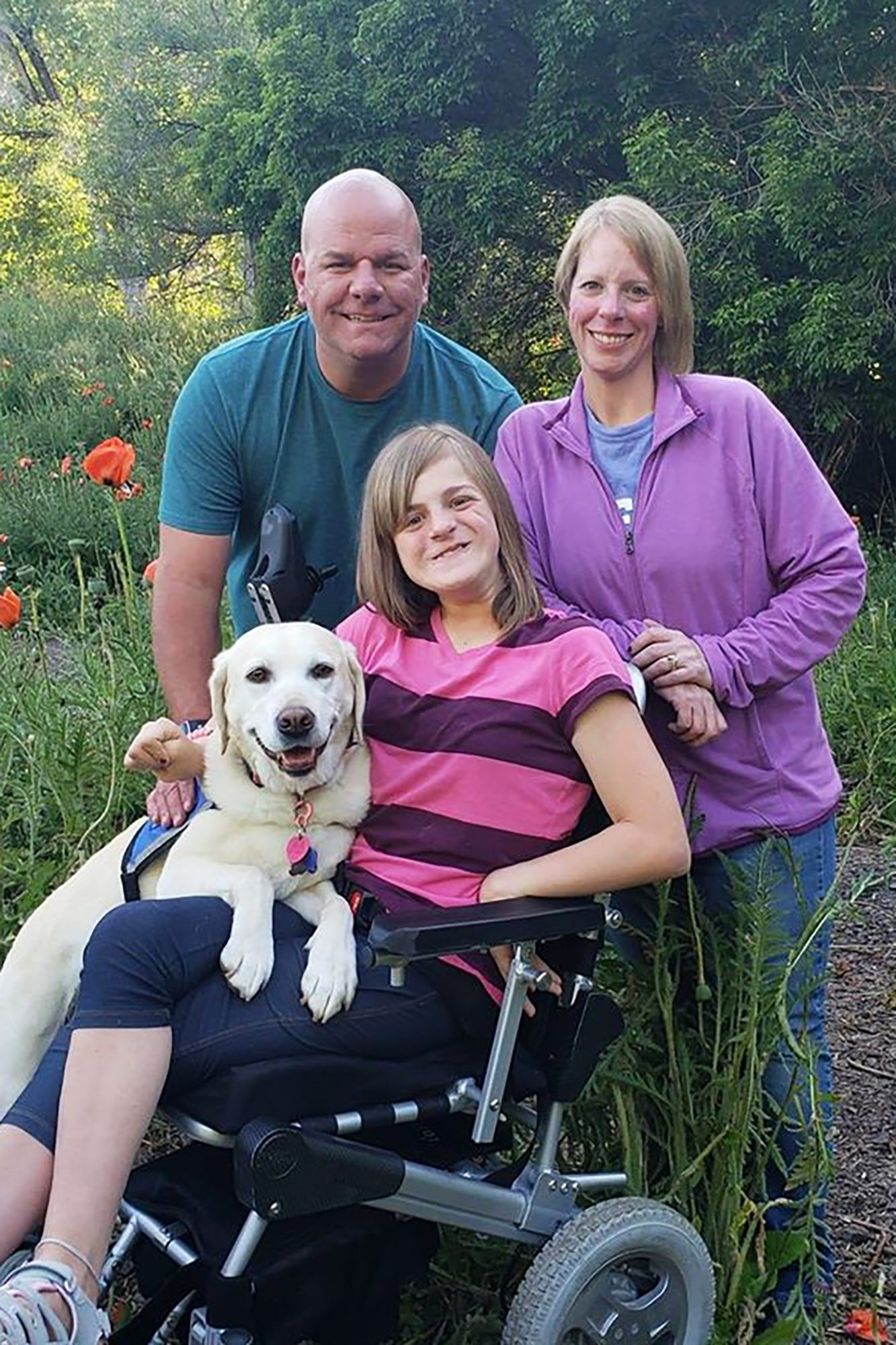 Emily the service dog with her handler and family