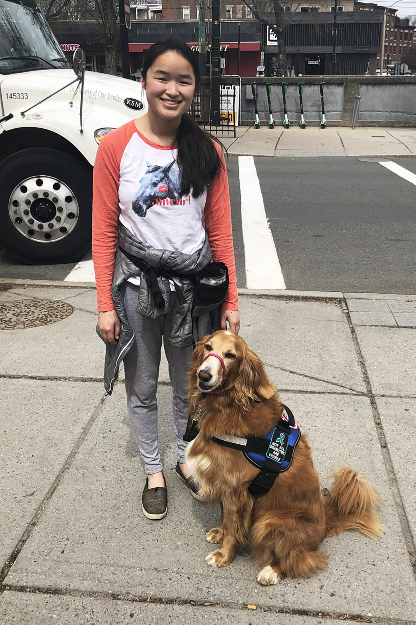 service dog handler with her goldendoodle service dog in vest