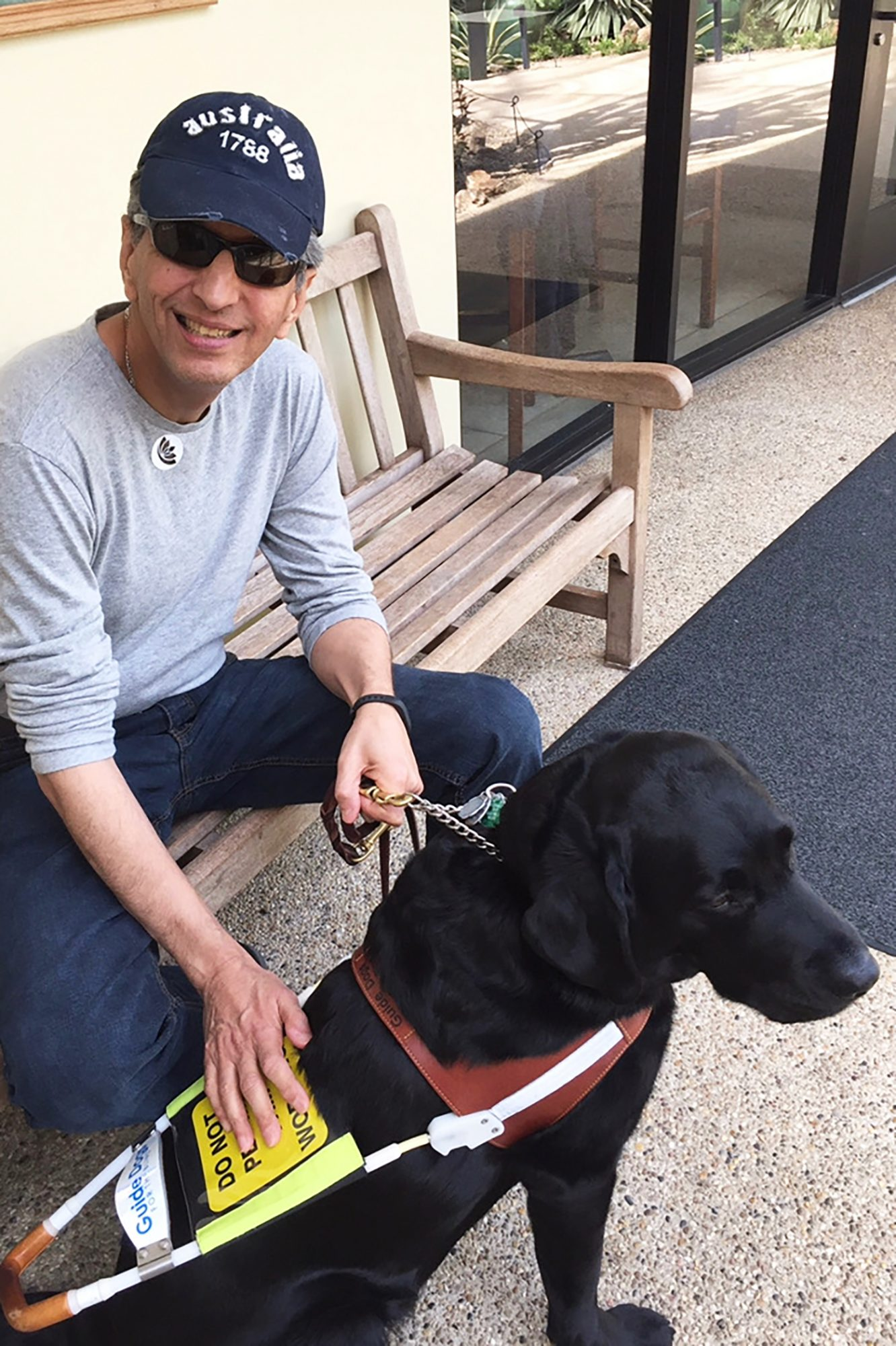 Nadir Mehta and his service dog Yamaha sitting on a bench
