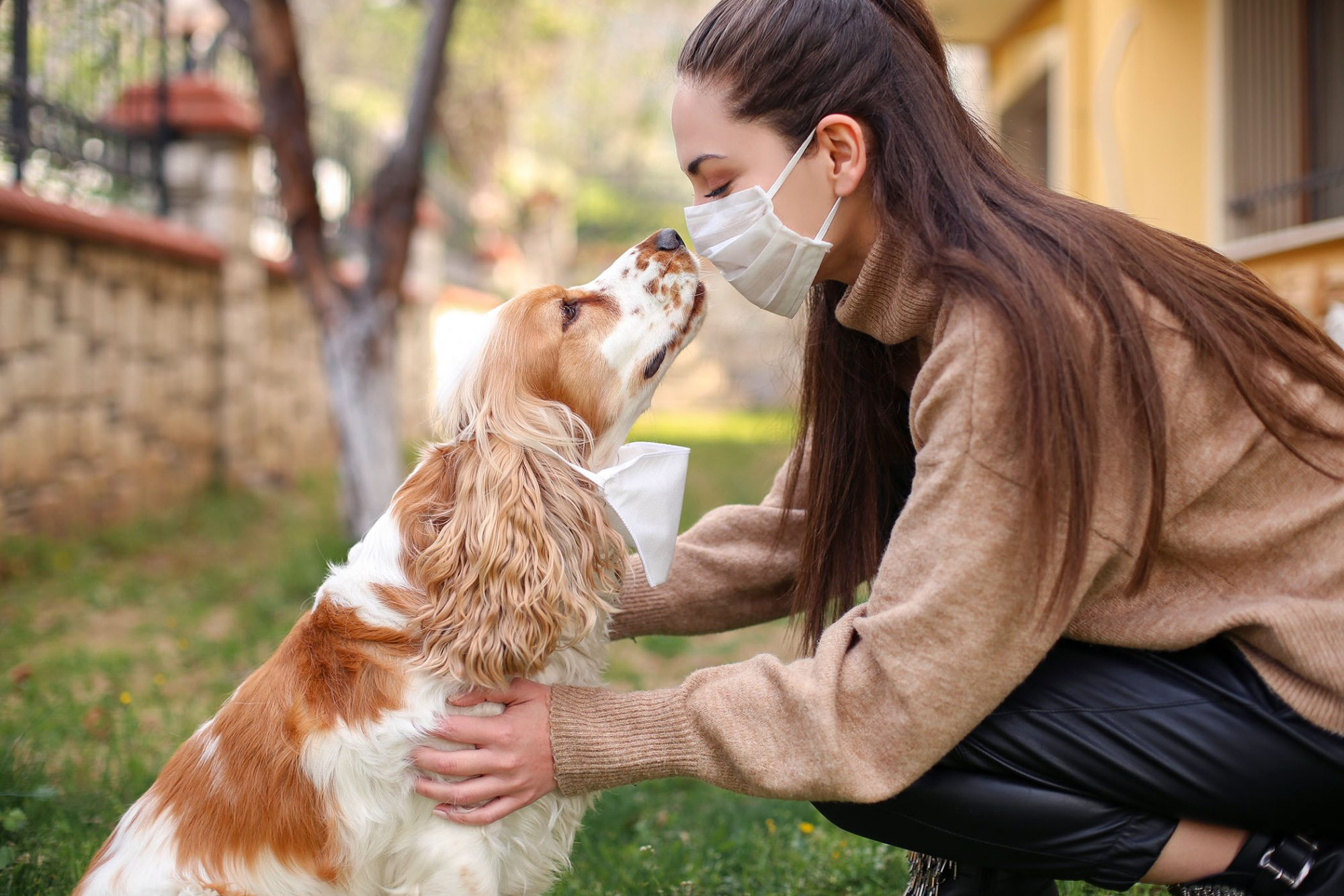 woman with mask looking at dog