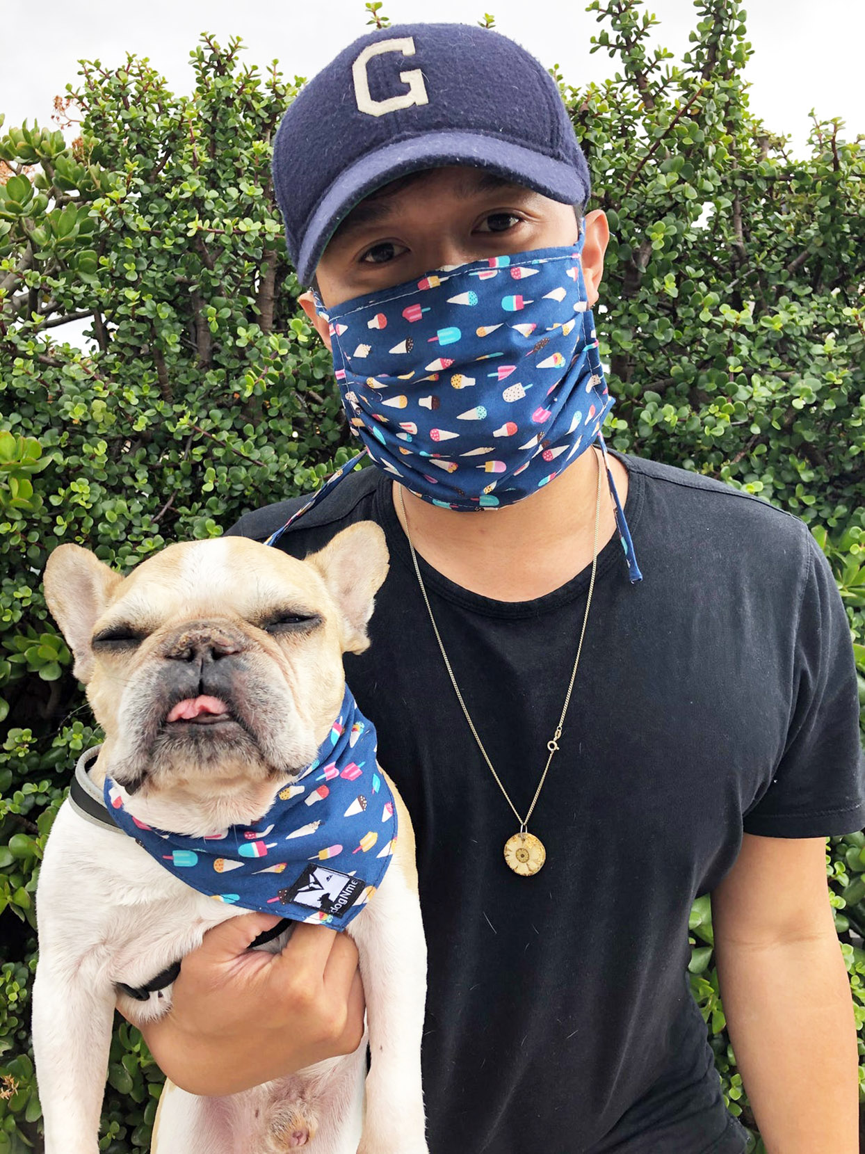 Person in cloth face mask poses with dog in matching bandana