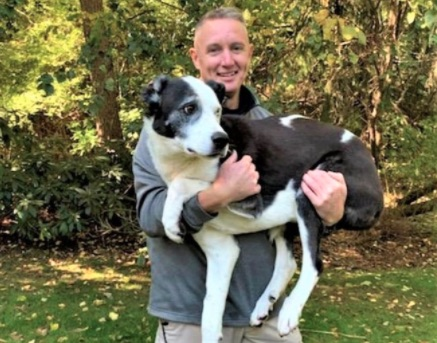man holds dog in arms