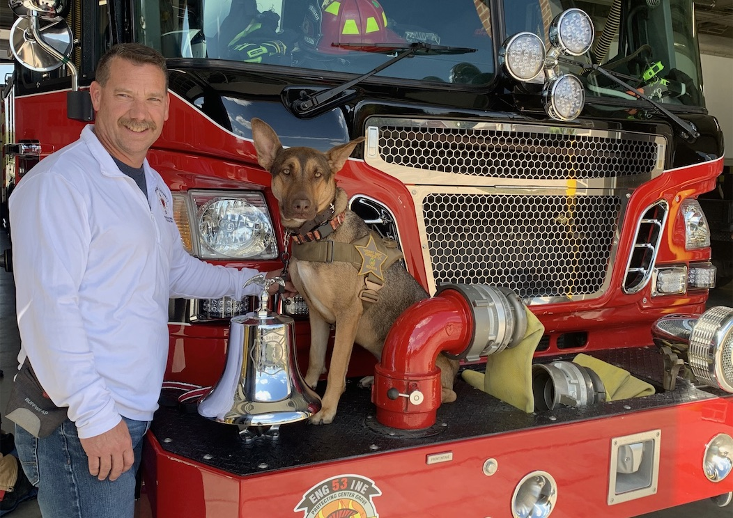 man with dog in front of fire truck