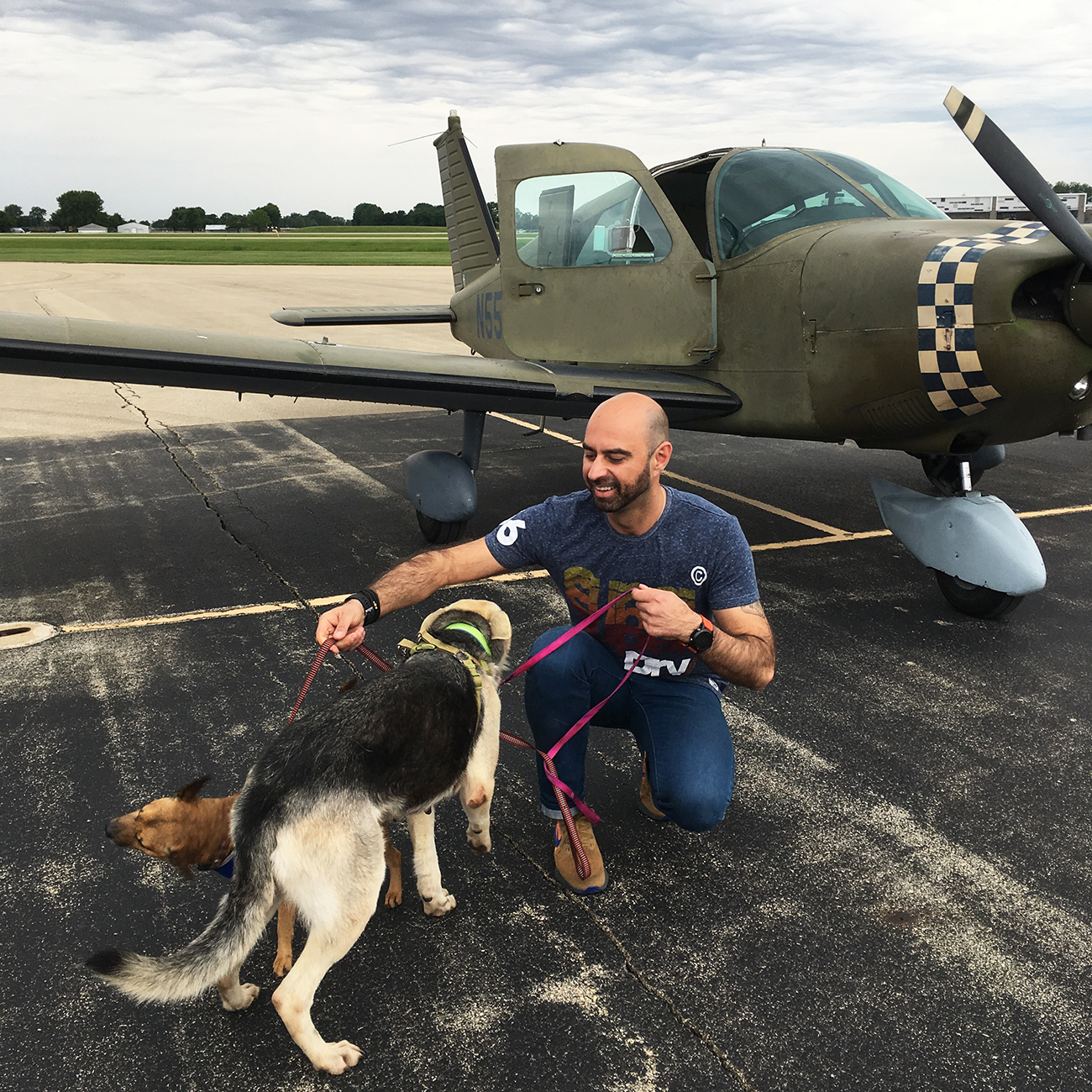 Eduard with two rescues dogs on tarmac with plane