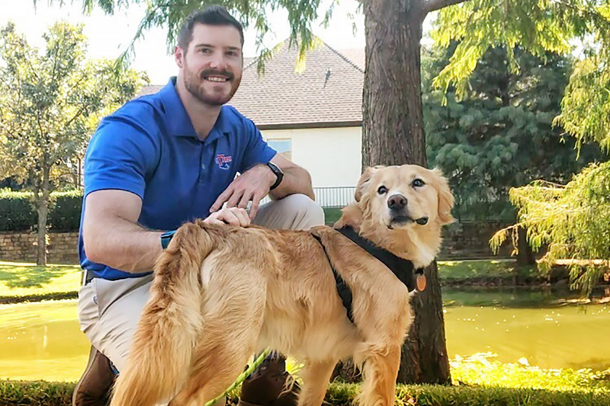 Dr. Hunter Finn with golden retriever in front of pond