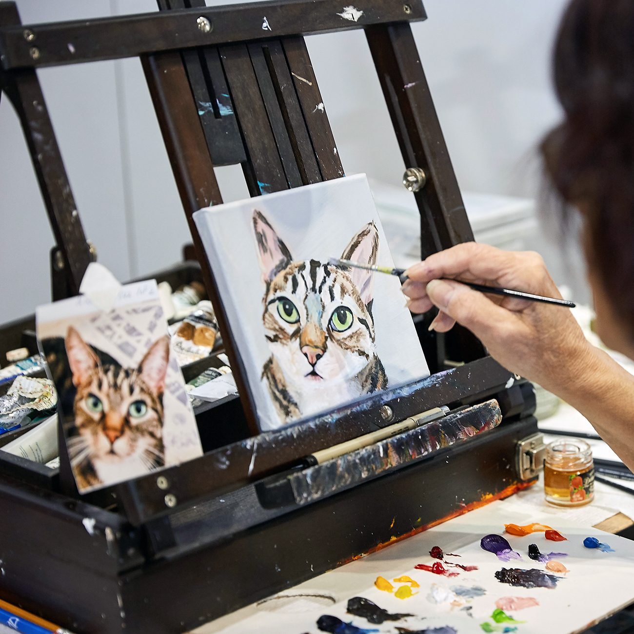 Artists hand painting cat portraits on easel