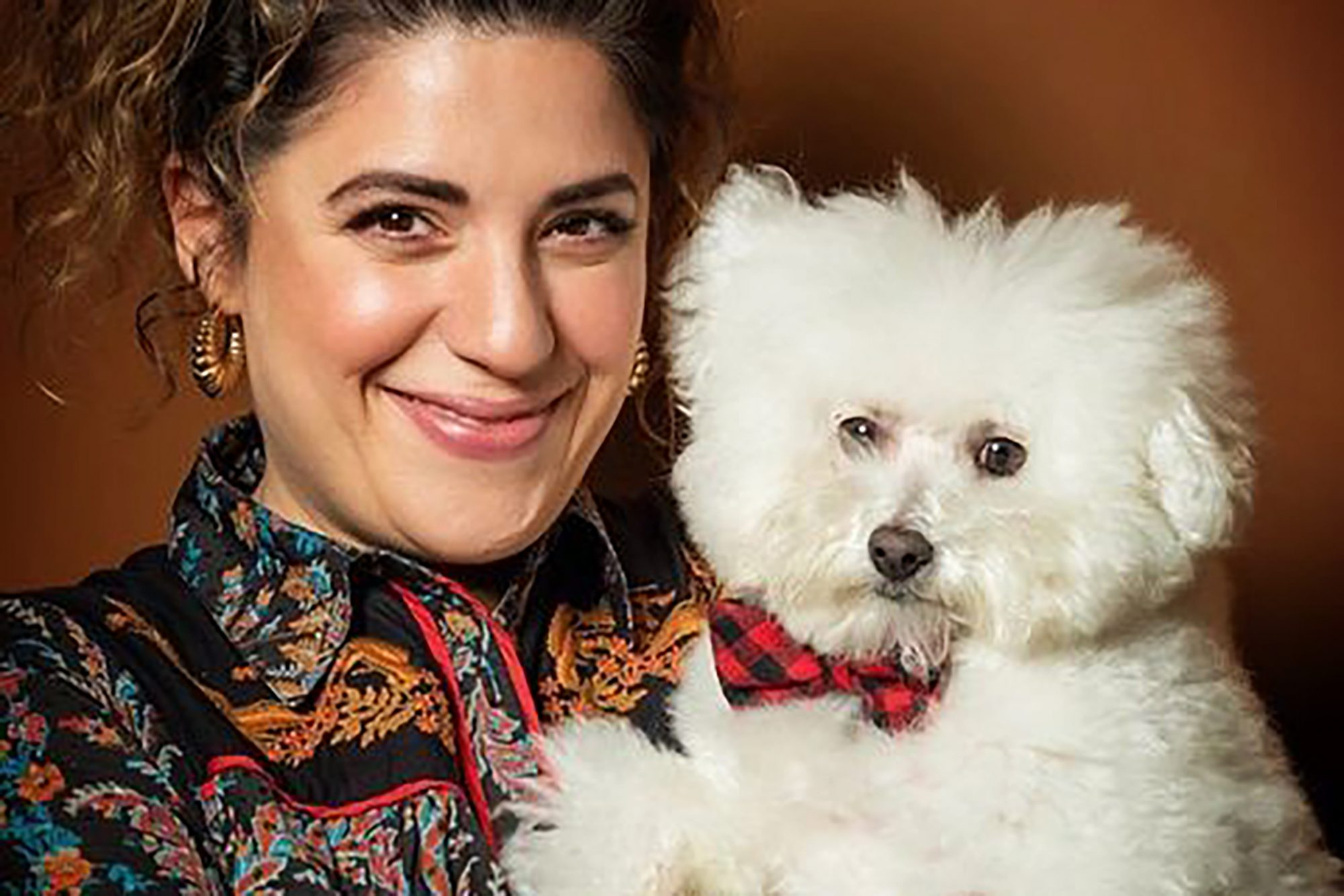 Portrait of dog groomer Jess Rona holding a white fluffy dog that has a bowtie
