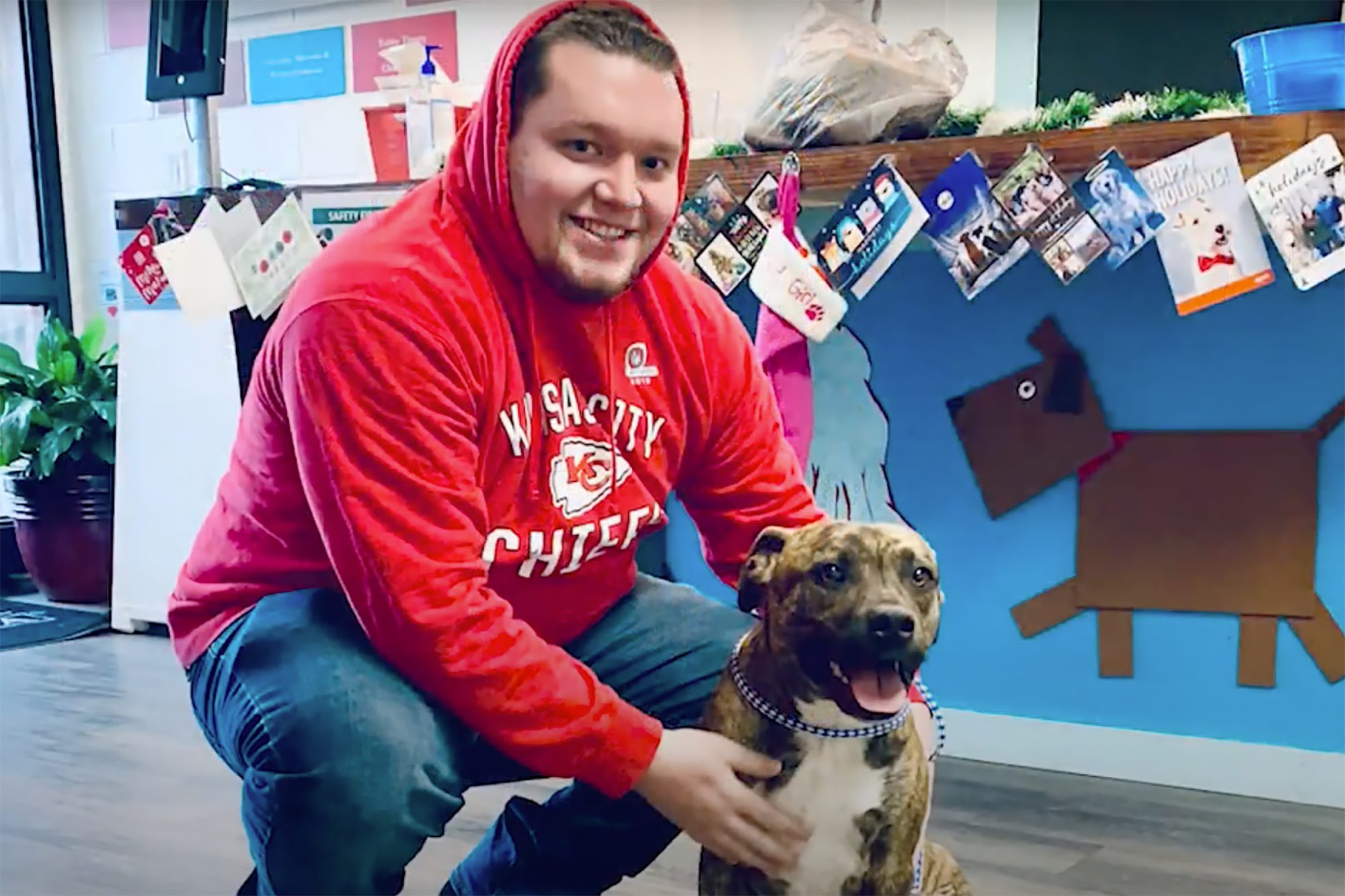 Man wearing Kansas City Chiefs sweatshirt embraces three-legged dog