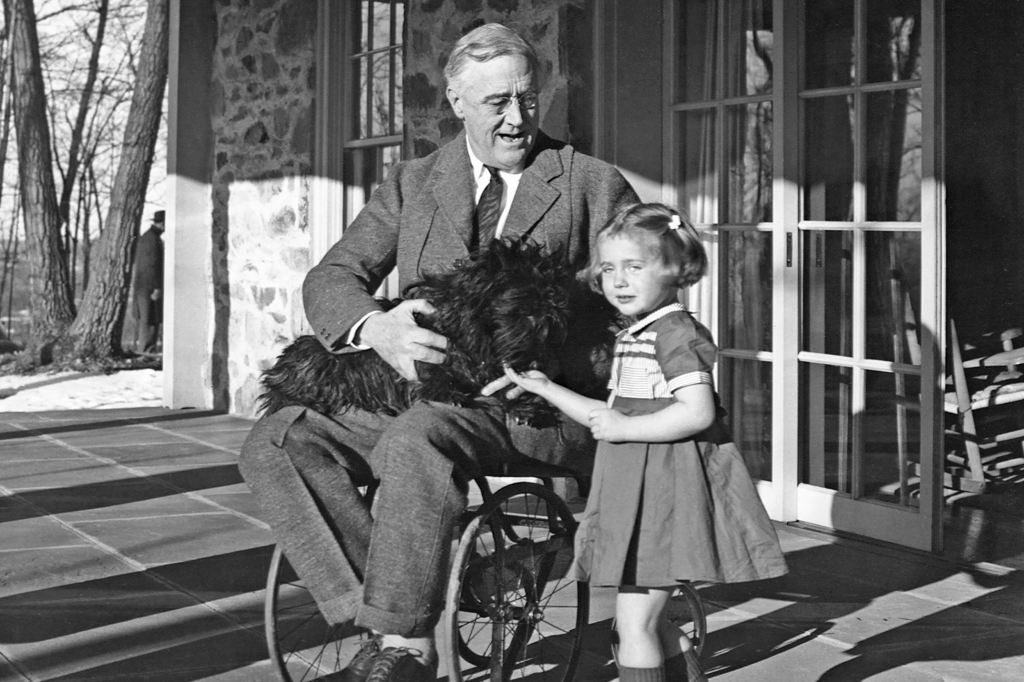 Photograph of Franklin D. Roosevelt with dog on lap and young girl standing next to him
