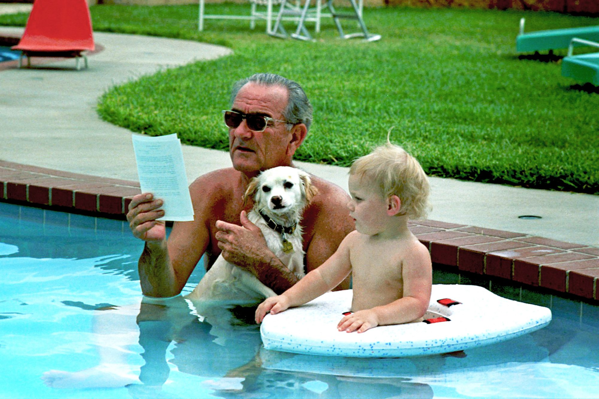 Photograph of Lyndon B. Johnson holding a white dog in a pool next to child