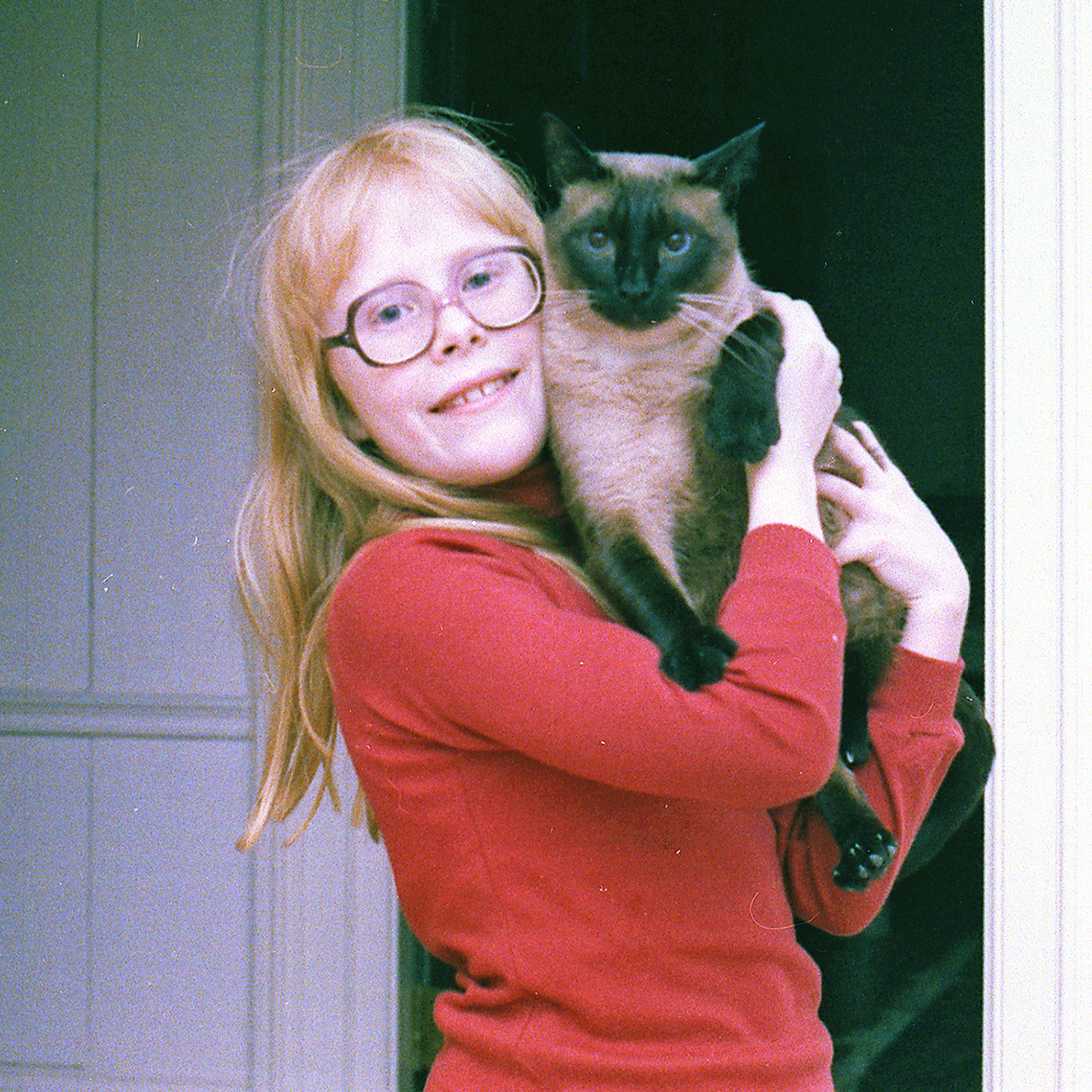 Photo of girl with glasses holding a tan cat