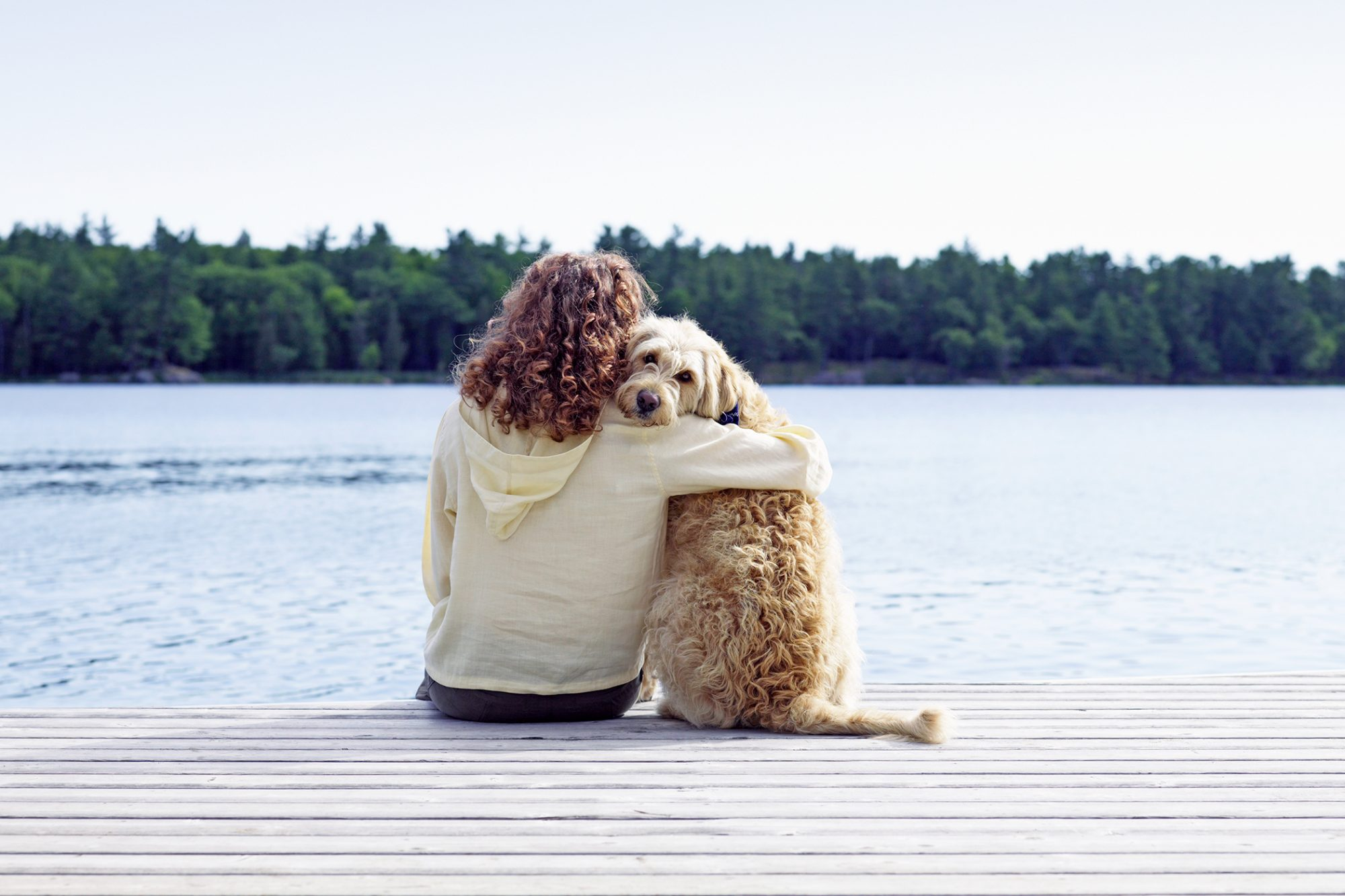 Woman embraces fluffy puppy on lake dock