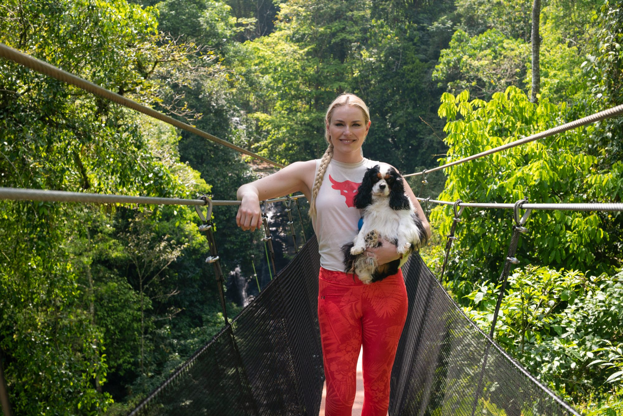 Olympian Lindsey Vonn holds spaniel puppy while standing on bridge