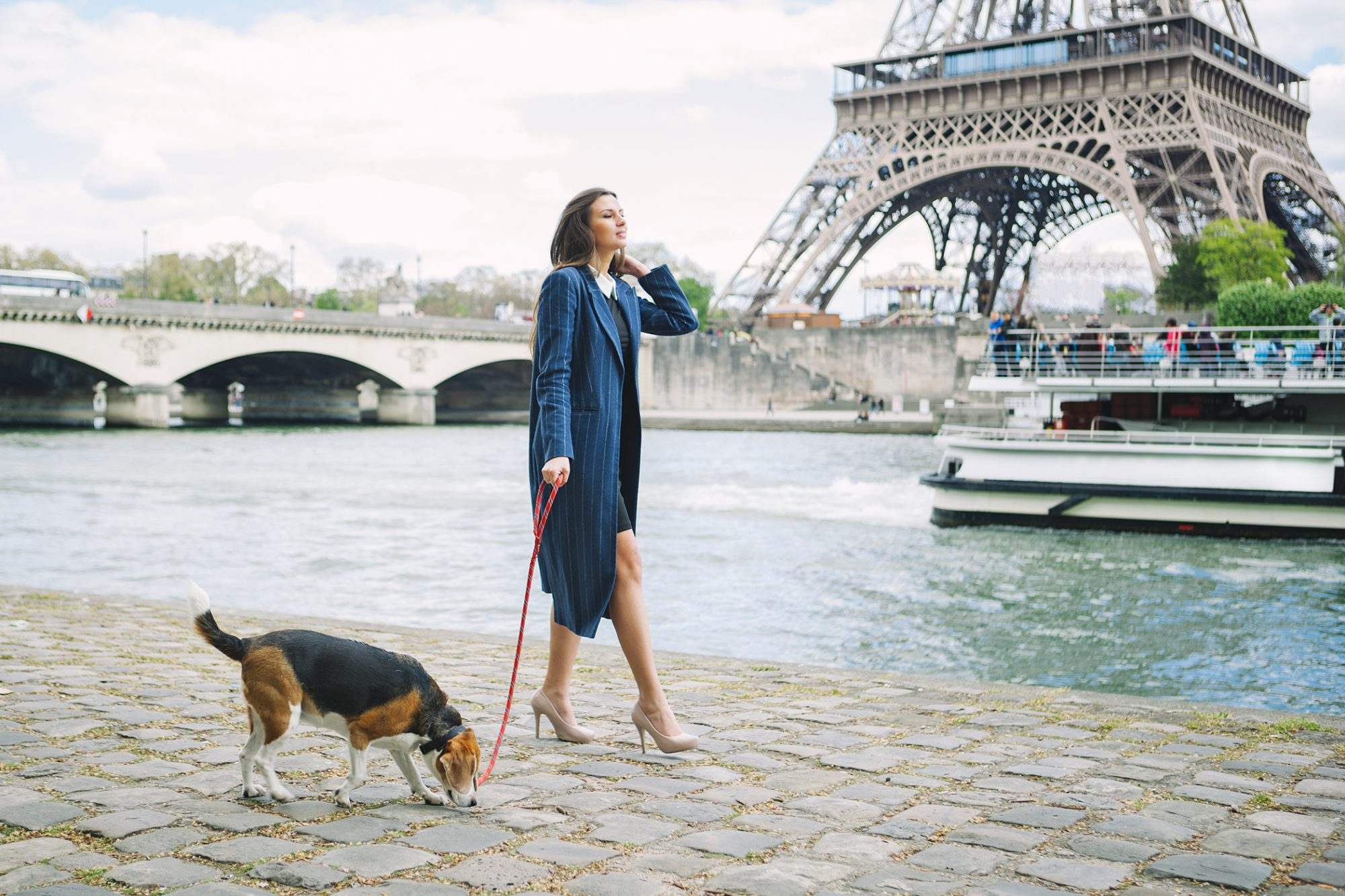 Woman in elegant outfit walks her dog by Paris river