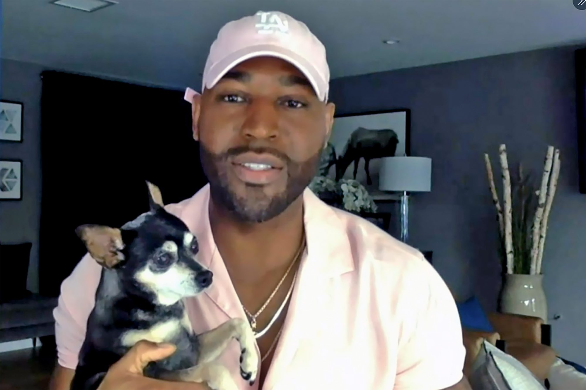 Celebrity host and lifestyle coach Karamo Brown holds small dog