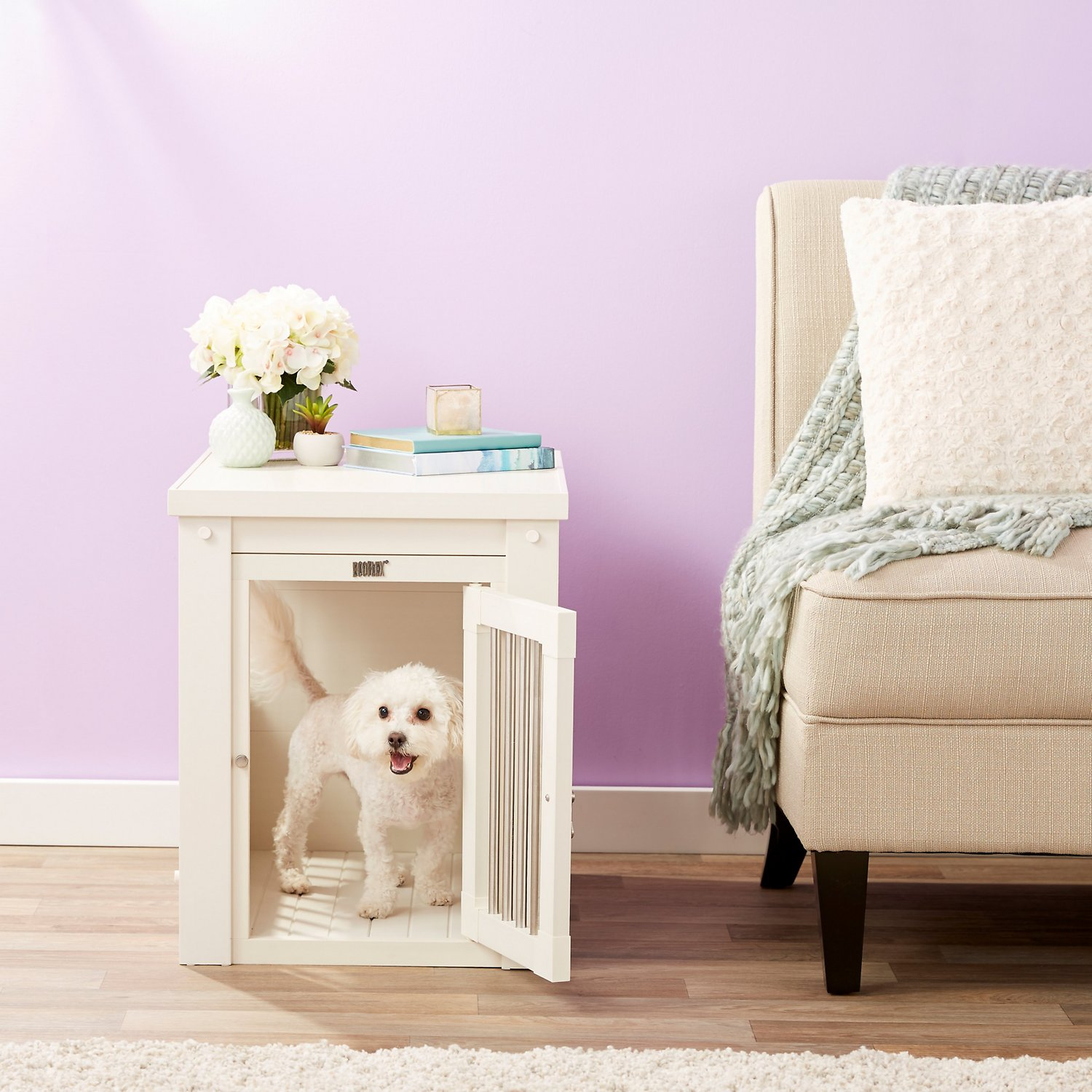 Furniture-style dog crate with a white dog inside in a living room