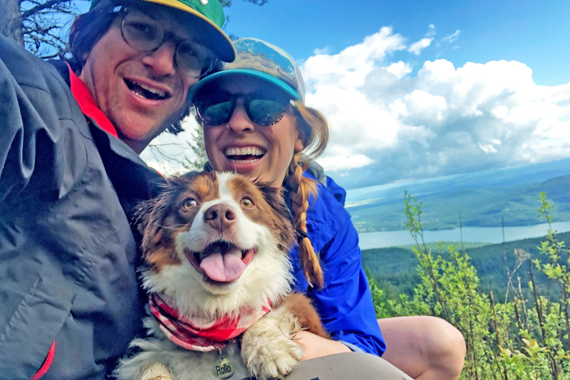 Couple embraces dog named Rollo on top of a hill