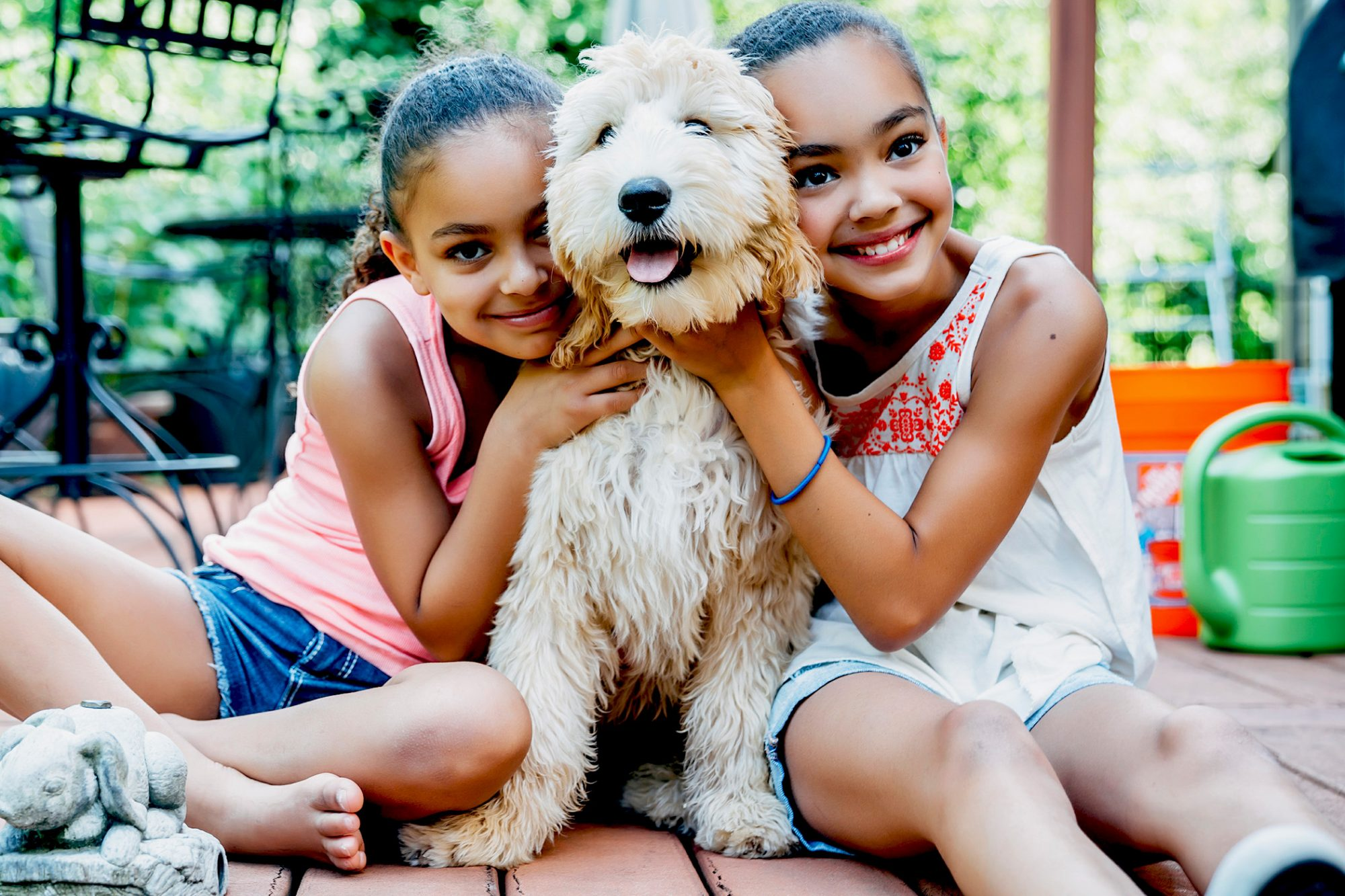 Two girls embrace blond labradoodle from both sides on outdoor deck