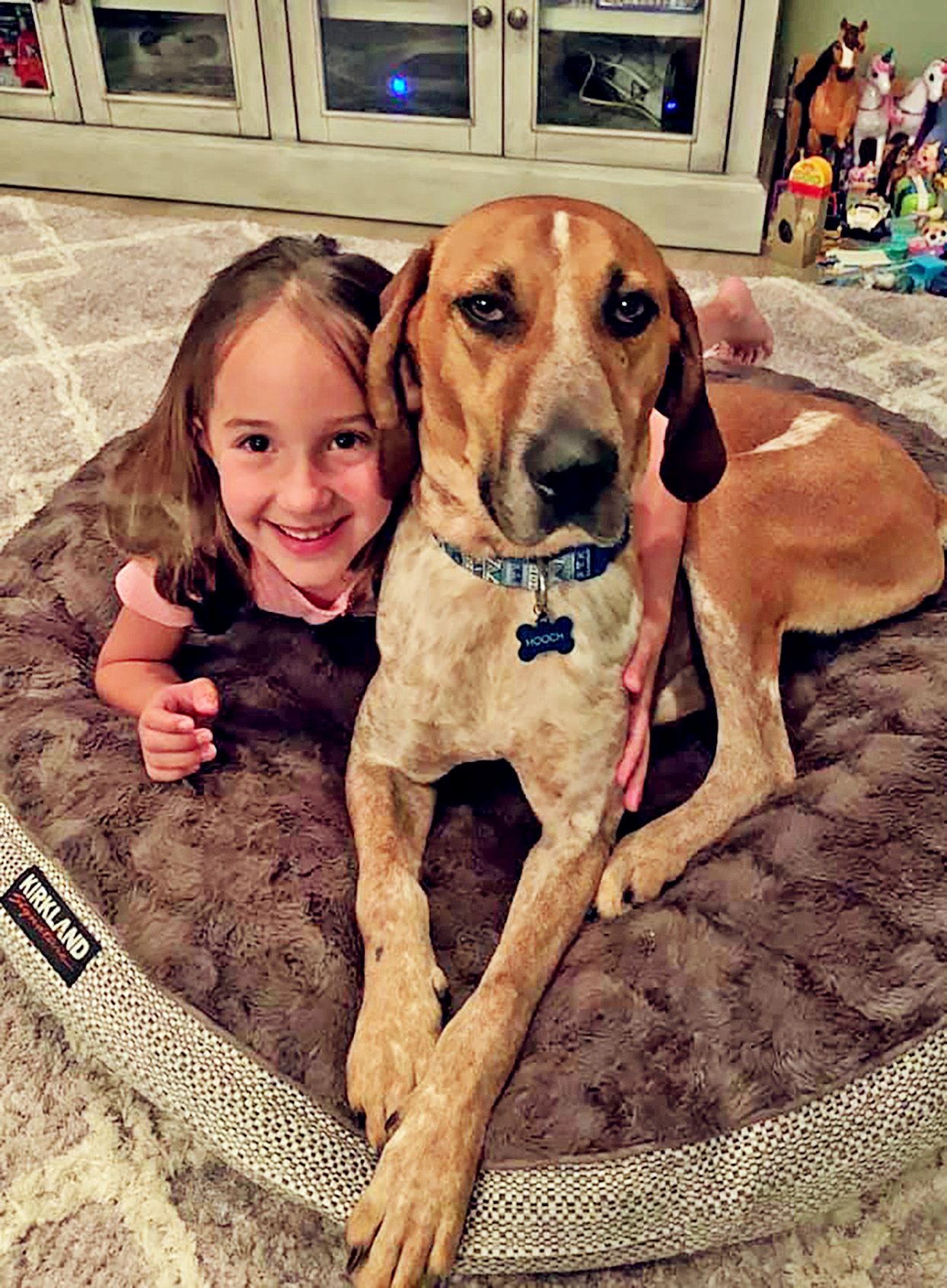 Little girl lays on dog bed with large dog named Hooch